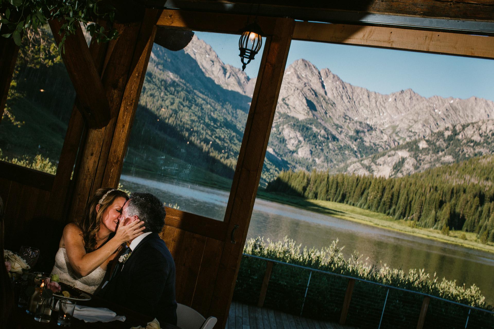 落基山婚礼照片-派尼河牧场婚礼在晚餐中分享一个吻