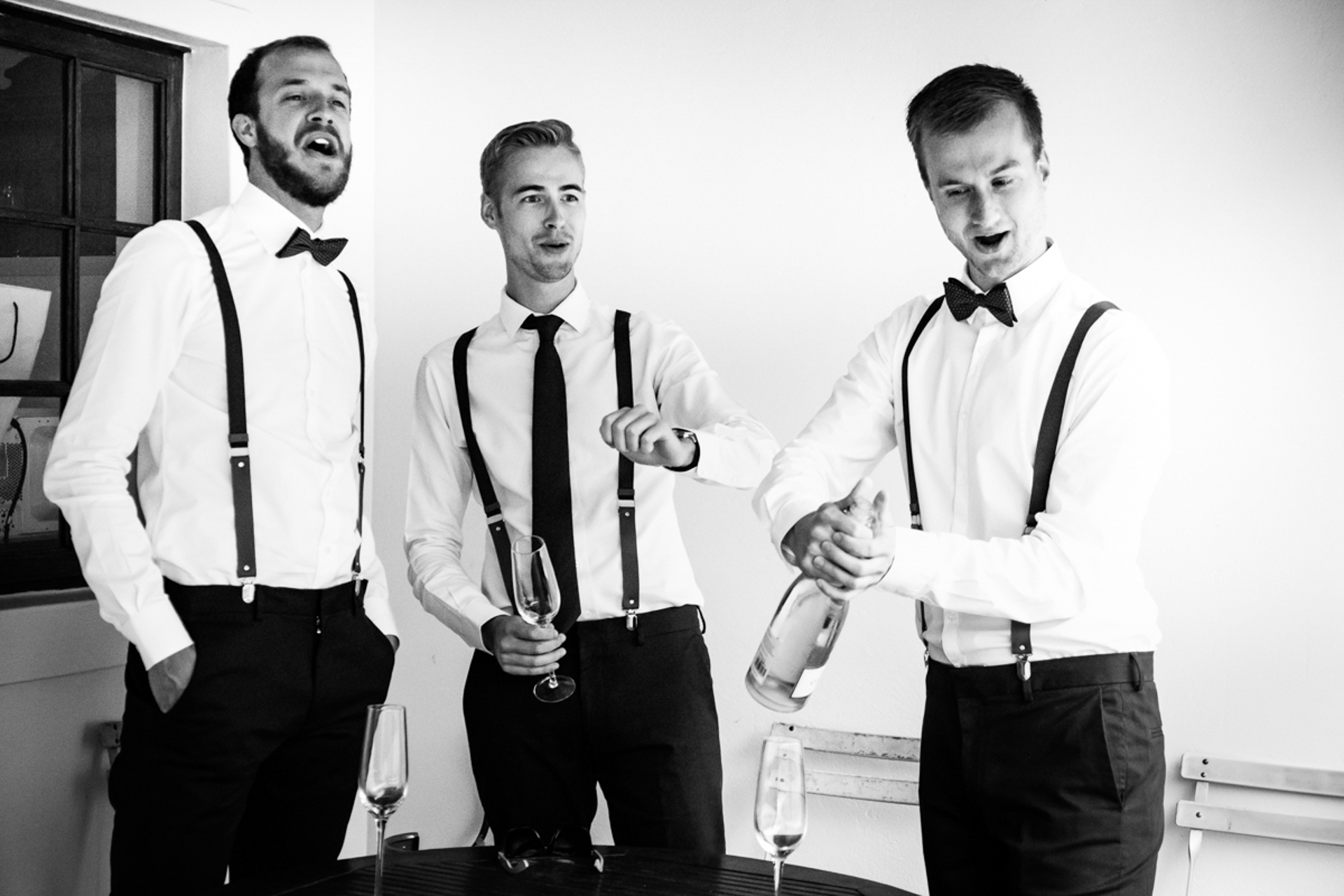Western Cape, SA Wedding Photographers | The groom and his groomsmen react to the opening of a bottle