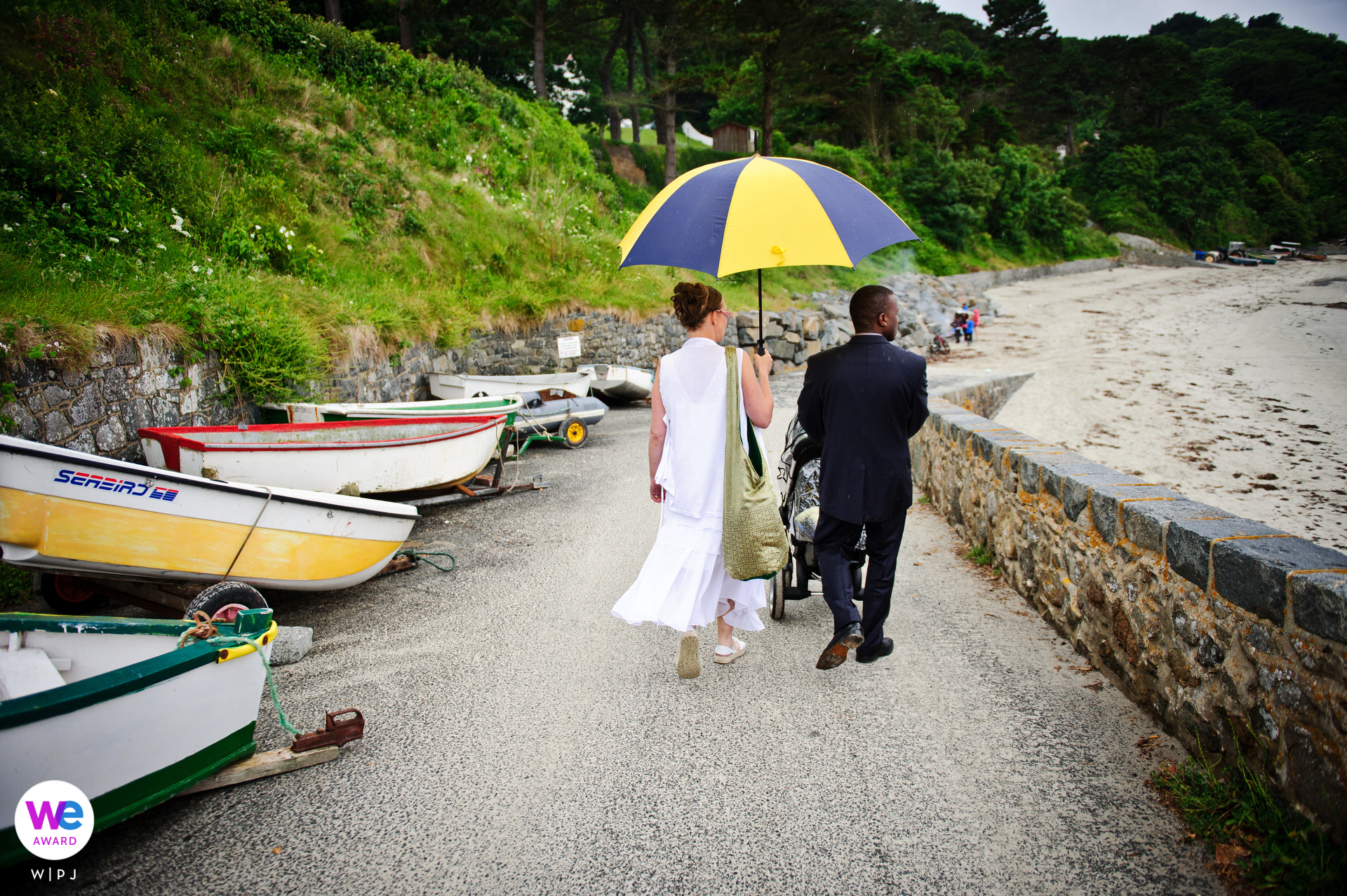 Portelet Harbour Wedding Day Photography | the bride and groom walk along the beach