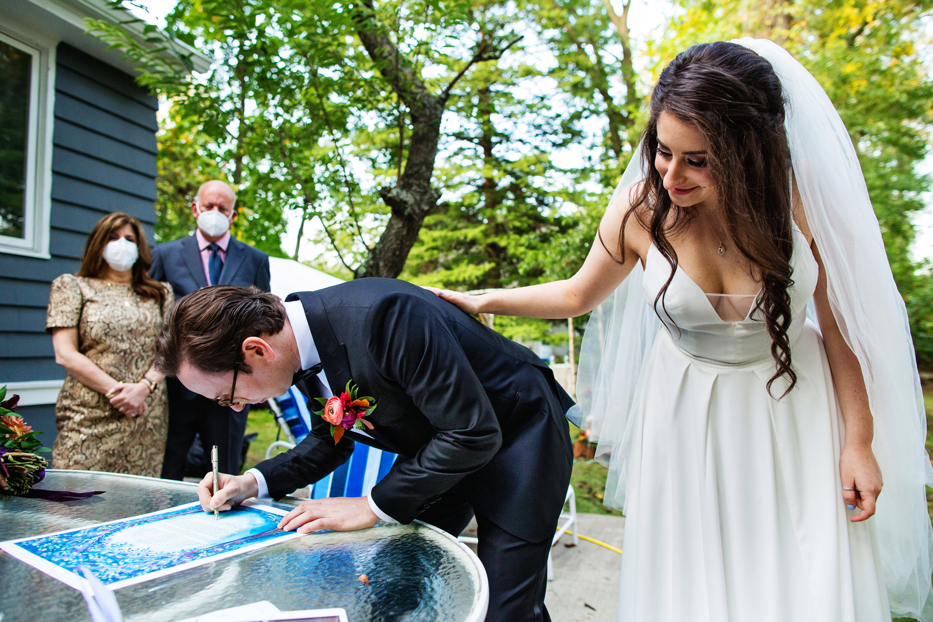 Montclair, New Jersey Backyard Wedding Photo | The groom signs their Ketubah