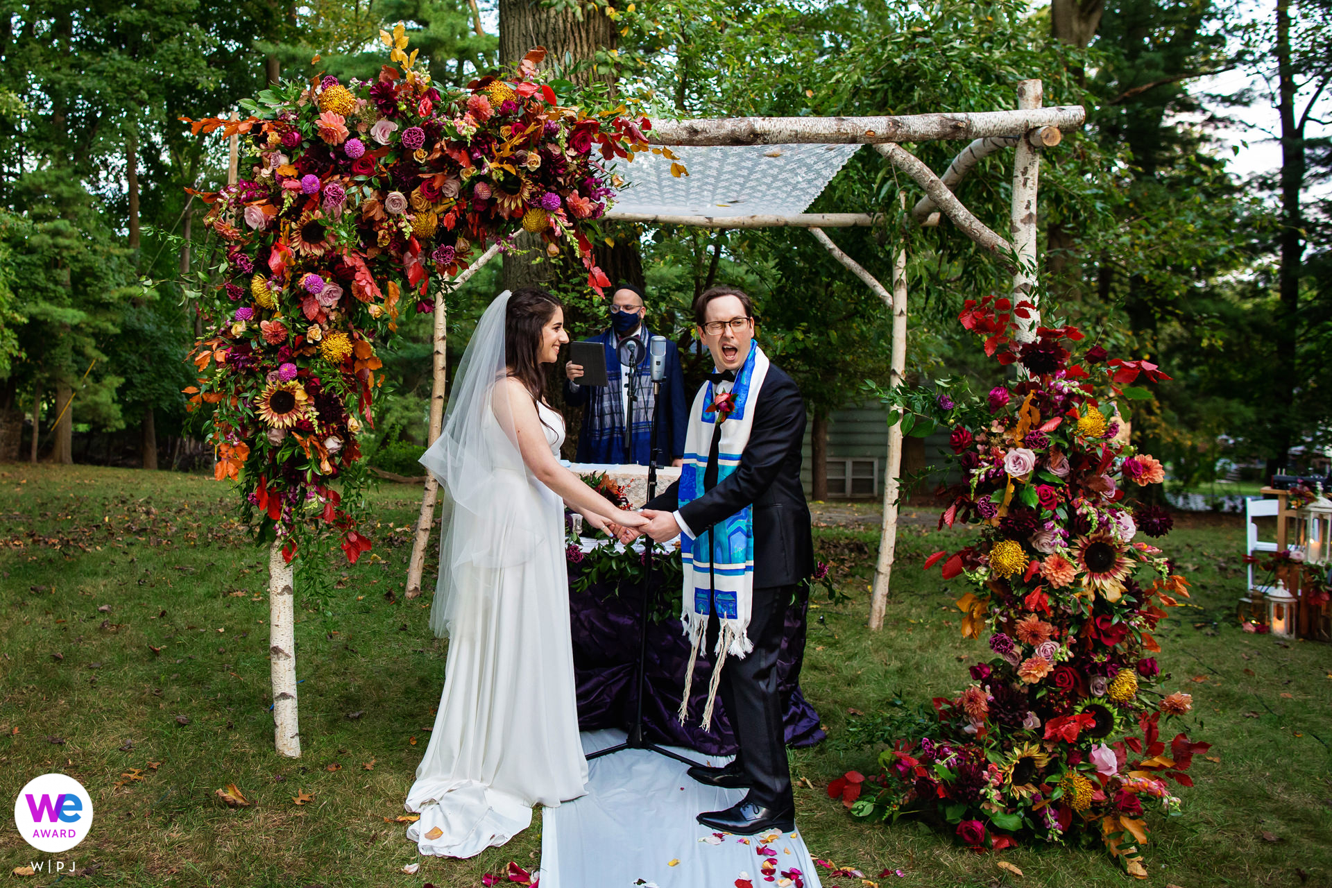 Montclair, New Jersey Outdoor Backyard Garden Wedding Photo created as The groom winks at the live stream camera for the guests at home