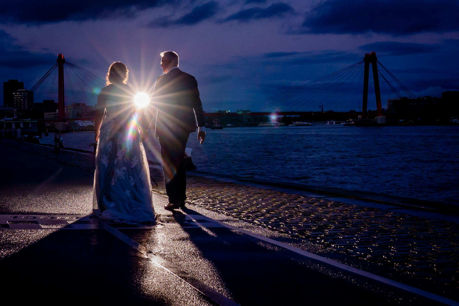 Wedding Photography - Rotterdam, Netherlands | The newlywed couple shares a romantic walk along the riverfront for portraits