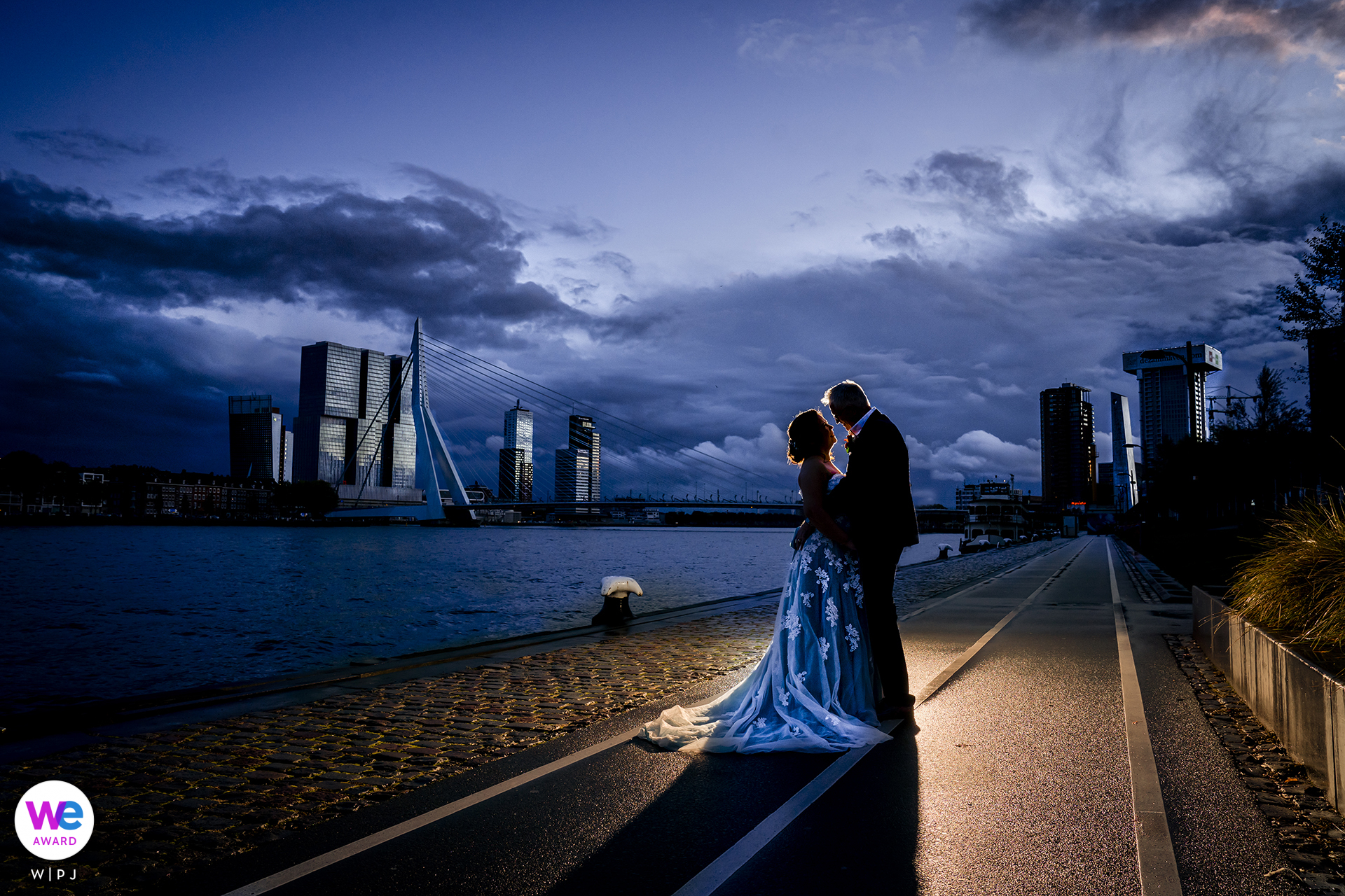 Professional Rotterdam Wedding Portrait of The bride and groom posing for a romantic image during blue hour