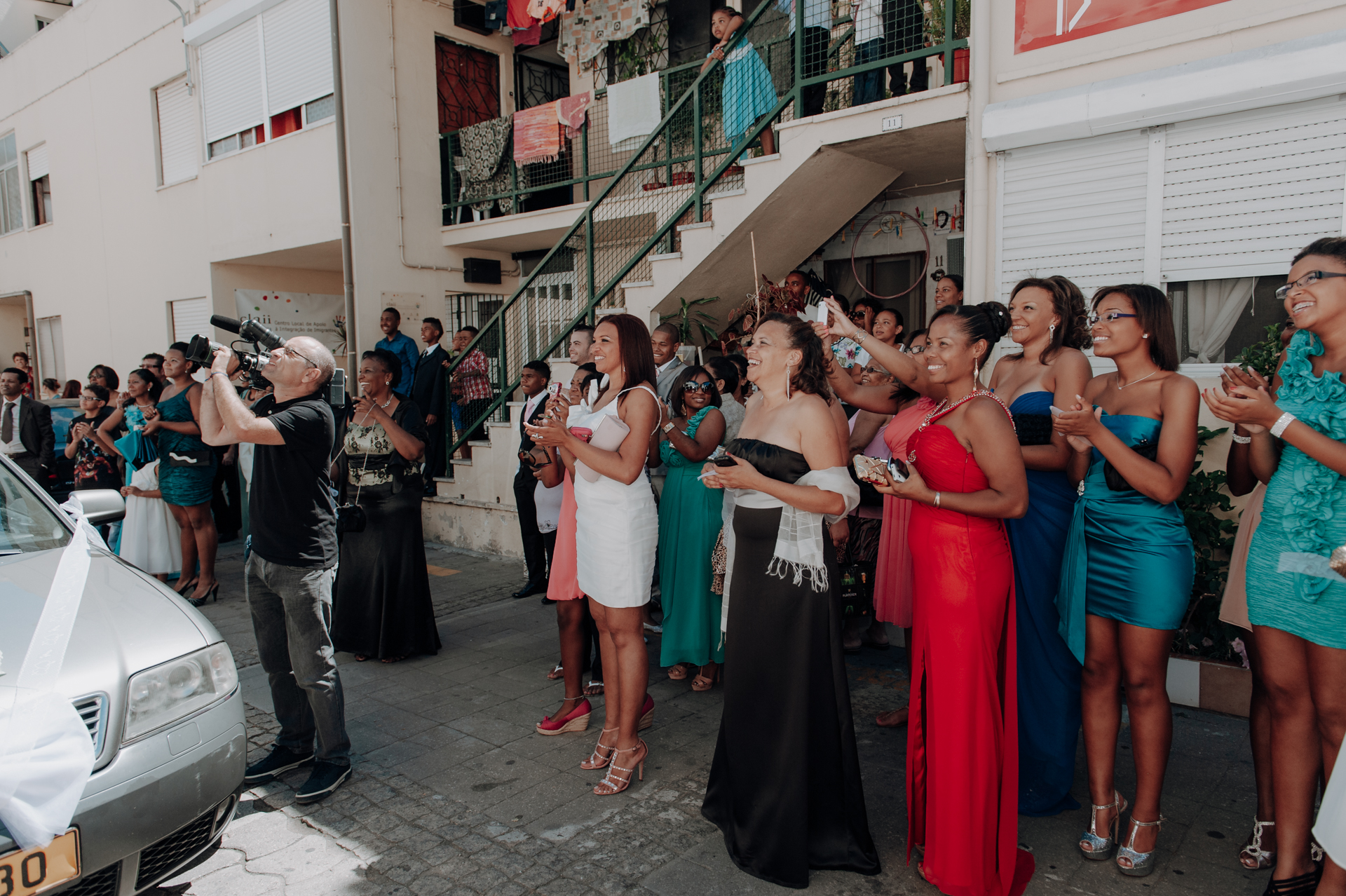 Portugal Wedding Photographers, Lisbon | Wedding guests and neighbors smile and cheer as the bride leaves her house