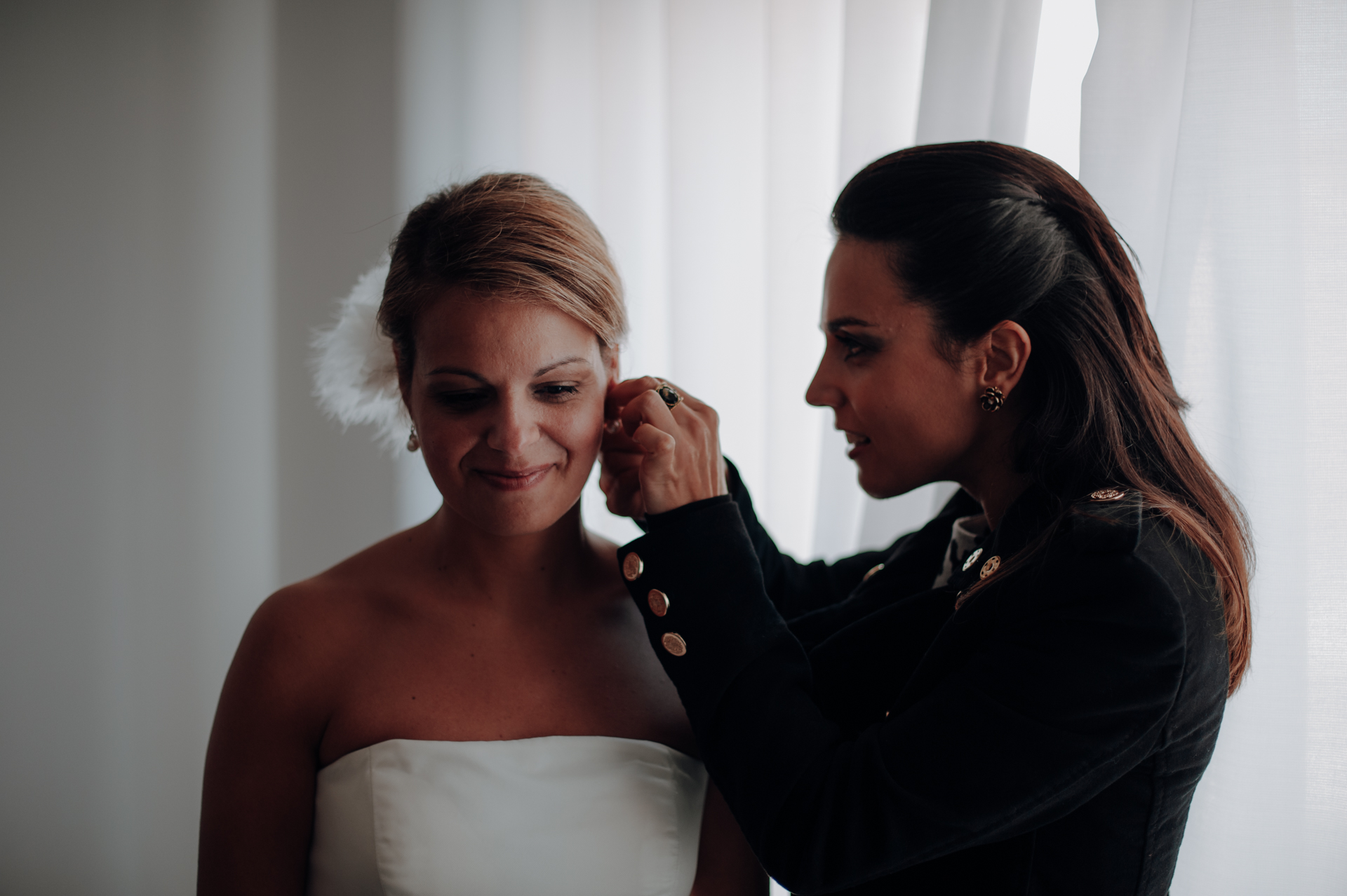 Lisbon, Portugal Wedding Photographers | The maid of honor fastens the bride's earrings