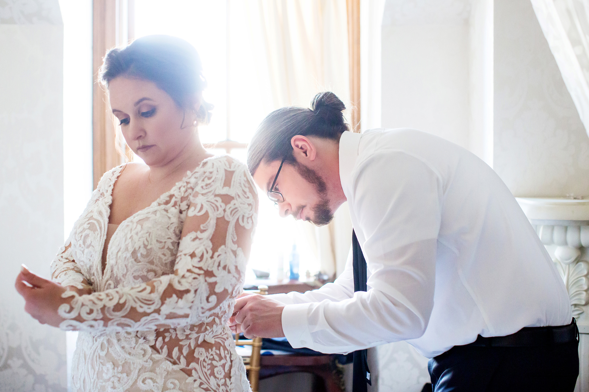 Gables LBI Wedding Picture, Beach Haven, NJ | The bride is preparing her gown with help from the groom