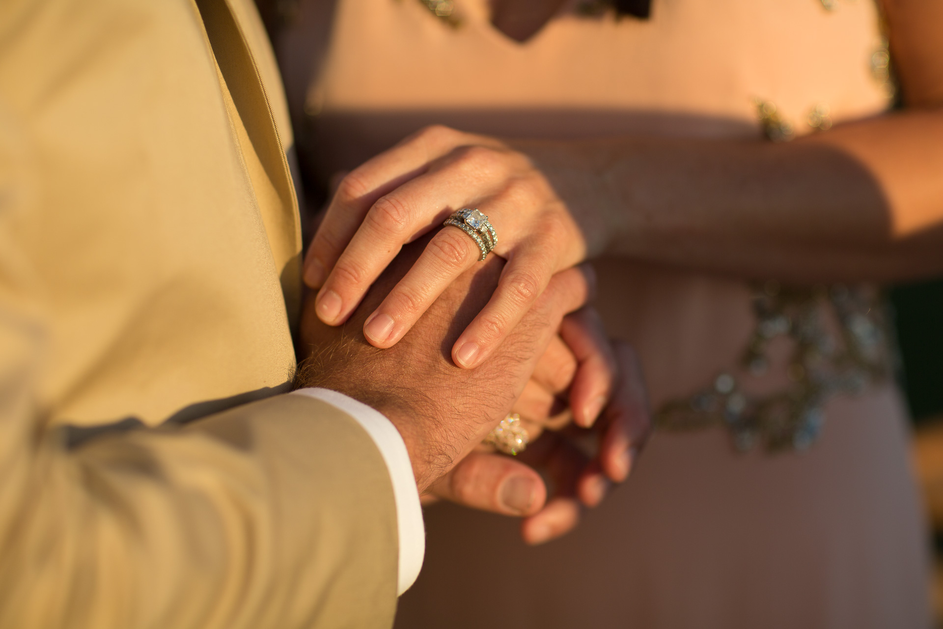 Casali Di Casole Detail Wedding Photo - Tuscany, IT | The bride and groom grasp each other's hands in a show of support