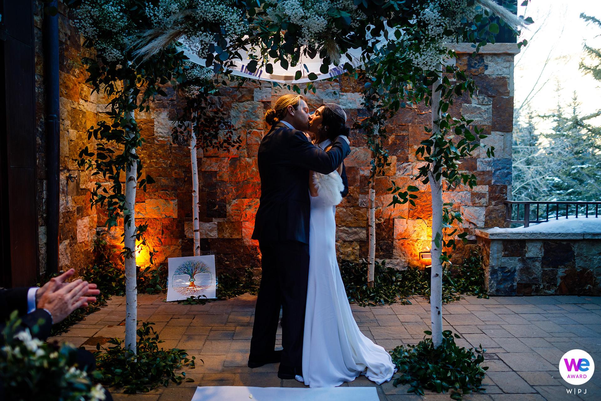 Vail, Colorado Cérémonie de mariage en montagne Photo du marié prenant sa nouvelle épouse dans ses bras et l'embrasse pour la première fois