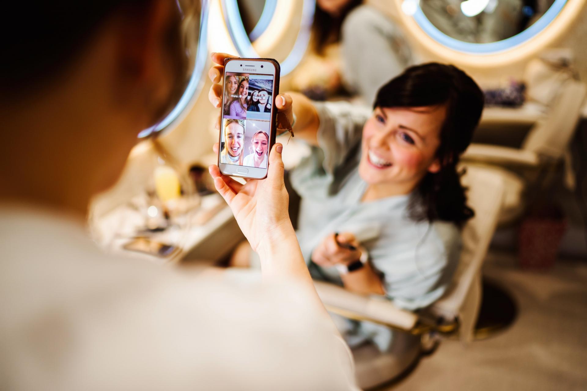 Fotografía de la boda de los graneros de Bassmead Manor | una dama de honor comparte su teléfono con la novia antes de la ceremonia