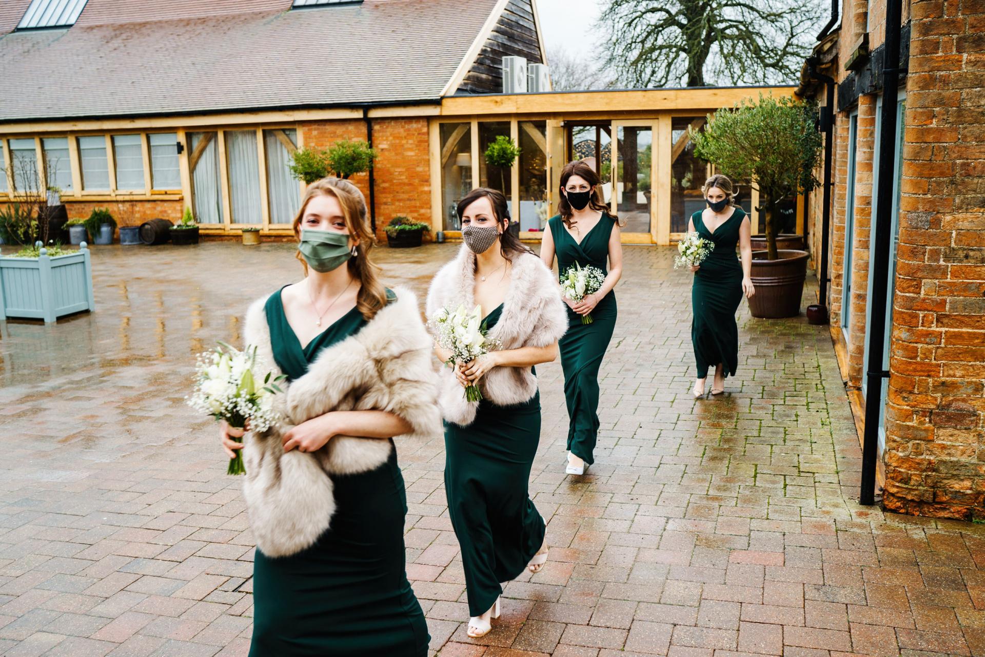 Bassmead Manor Barns Fotografía de bodas | Las damas de honor se van a la ceremonia con vestidos verde oscuro.