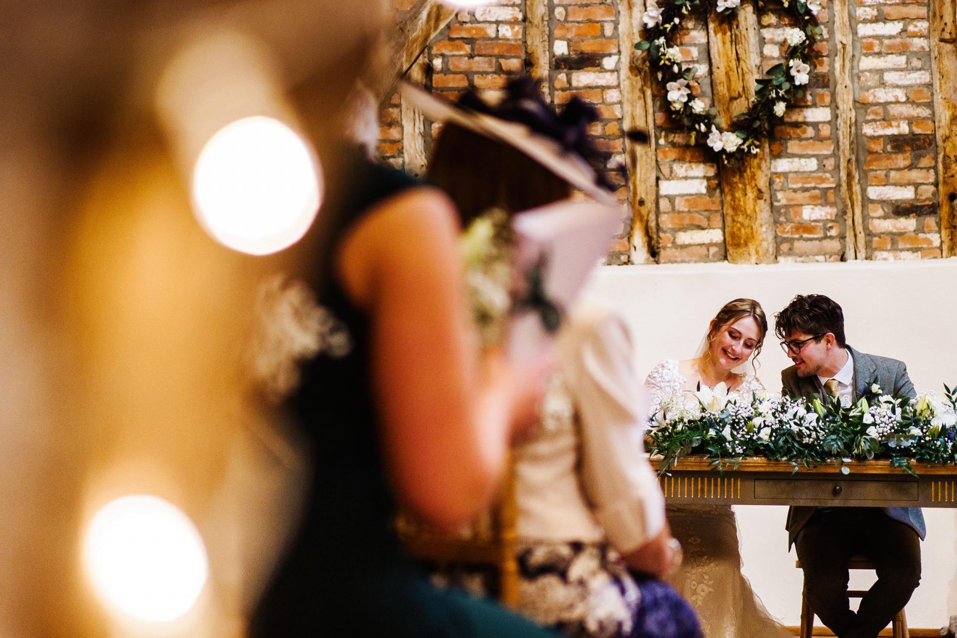 Imagen de boda de Bassmead Manor Barns St Neots | Echando un vistazo a algunos invitados, podemos ver a los novios sentados en una mesa.