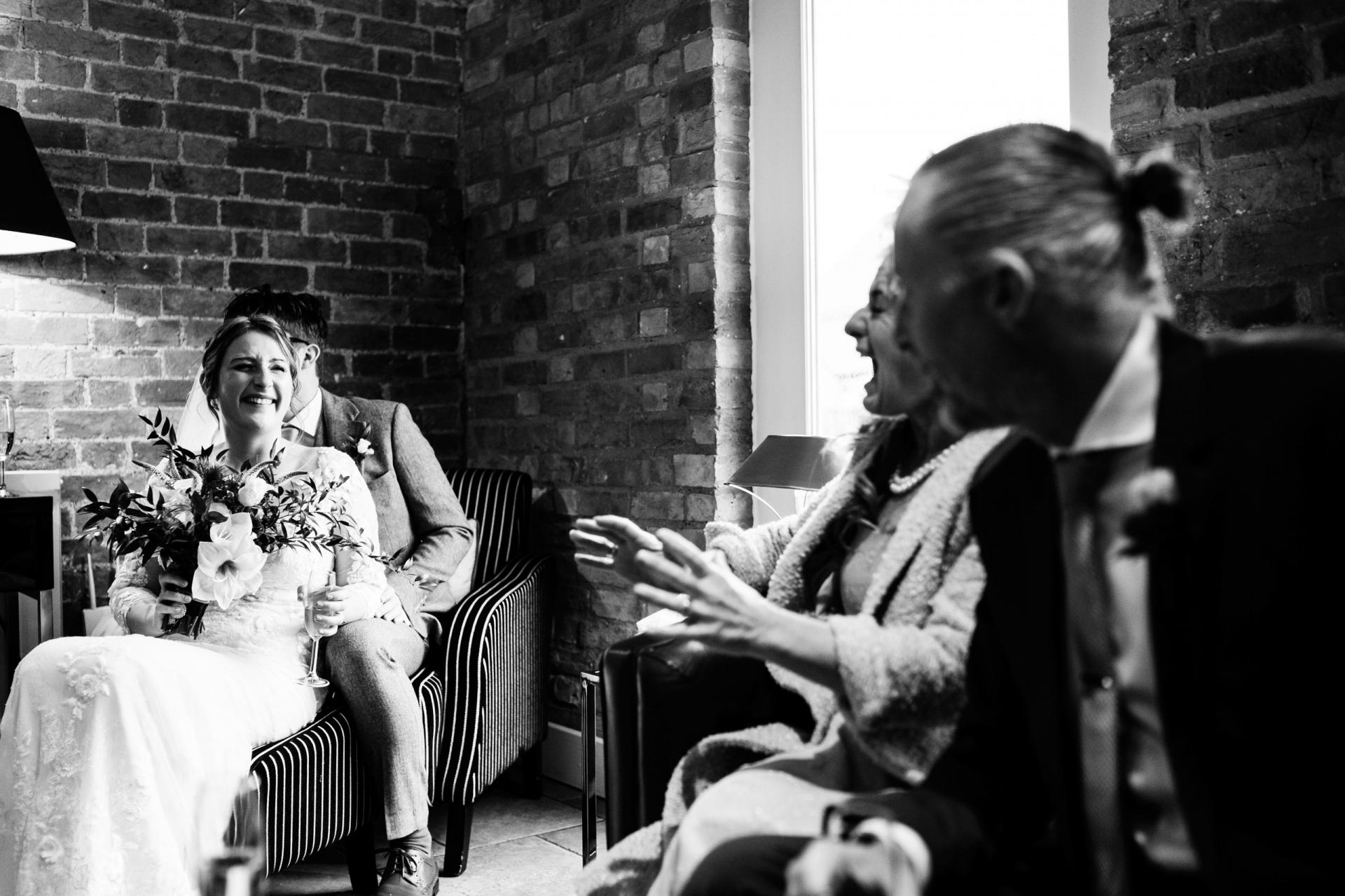 Imagen de boda del Reino Unido - Bassmead Manor Barns, Cambridgeshire | La novia y el novio, sentados juntos en una silla,