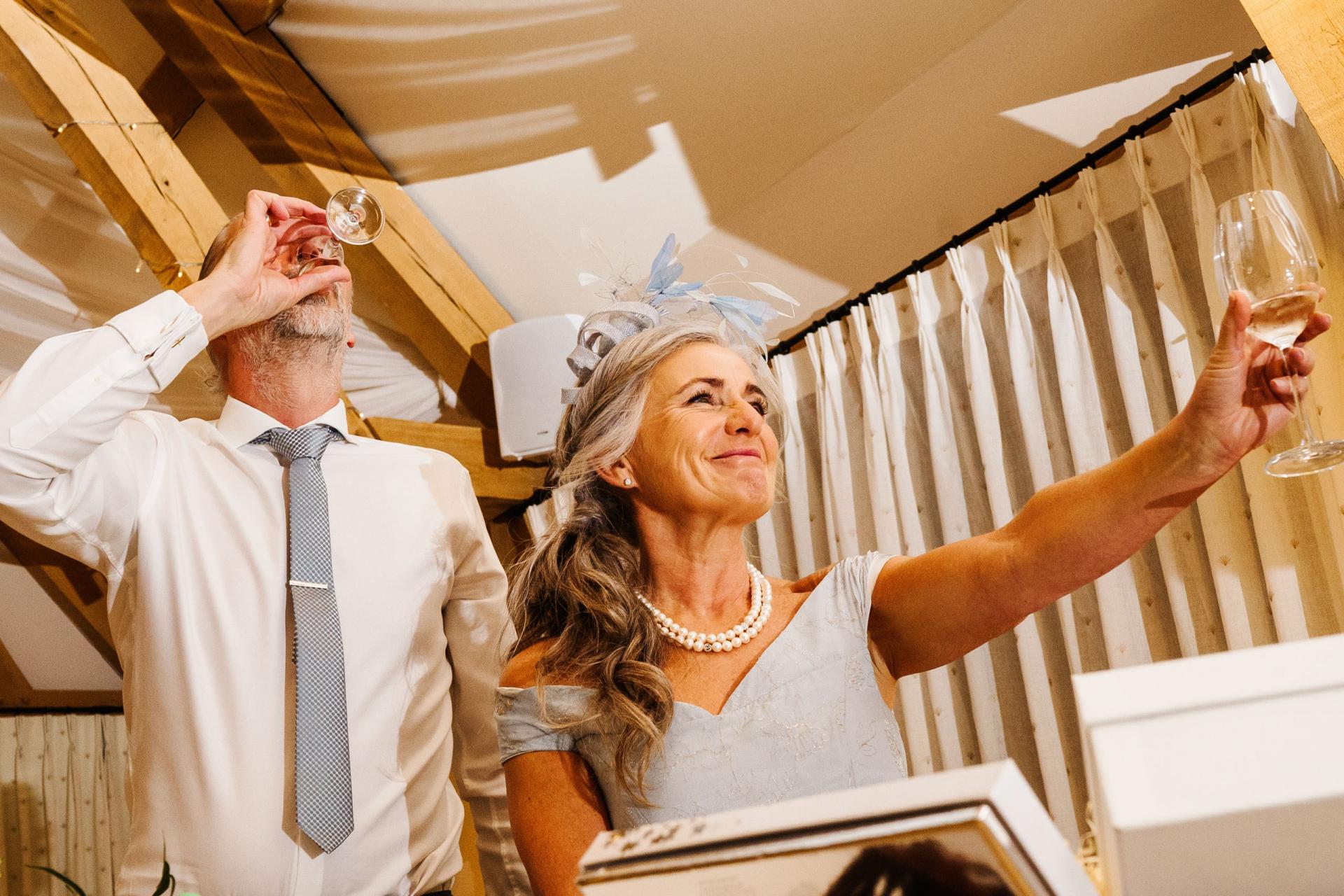 Fotógrafos de bodas de Bassmead Manor Barns, Reino Unido | La madre del novio brinda por la feliz pareja