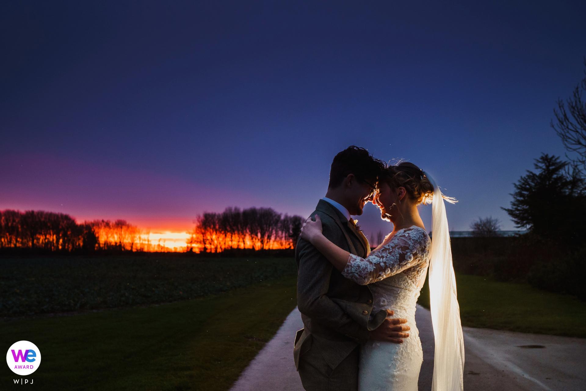 Granero Foto del lugar de la boda - Cambridgeshire, Bassmead Manor Barns | en la última luz del día después de su boda, justo cuando el sol comienza a ponerse