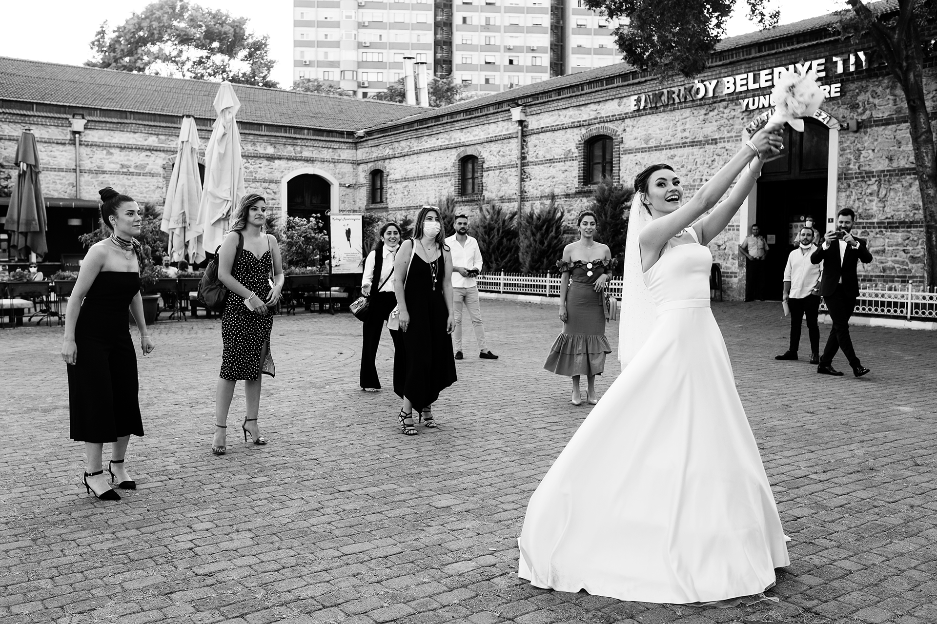 Local Municipality Belediye Istanbul, Turkey Wedding Image | Tossing bridal bouquet in front of the registry office