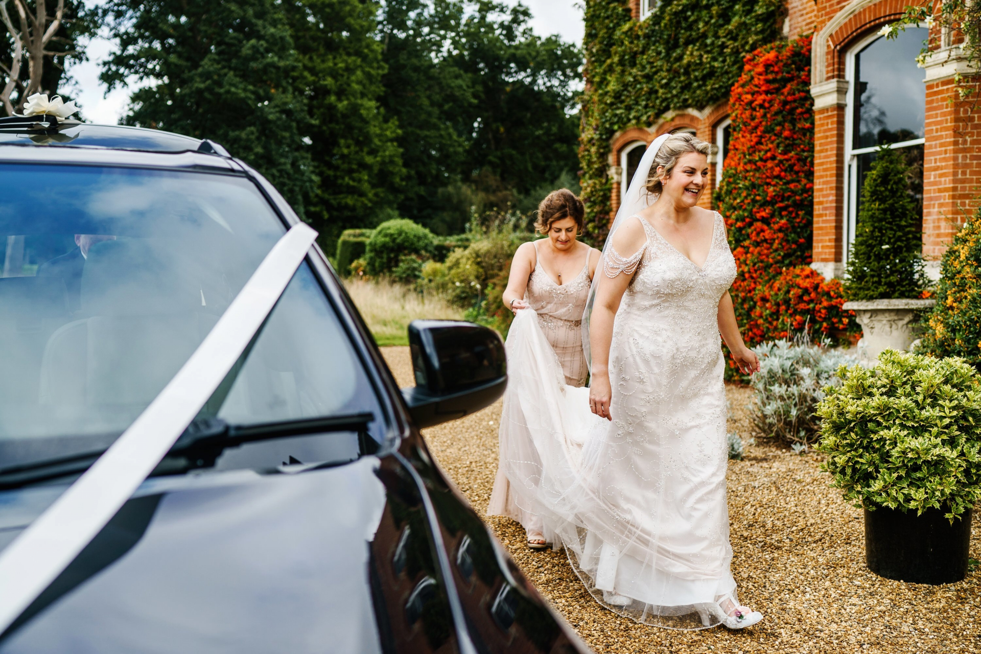 Gunthorpe Hall Wedding Photography | one of the bridesmaids helps the bride with her train as she walks along a gravel path