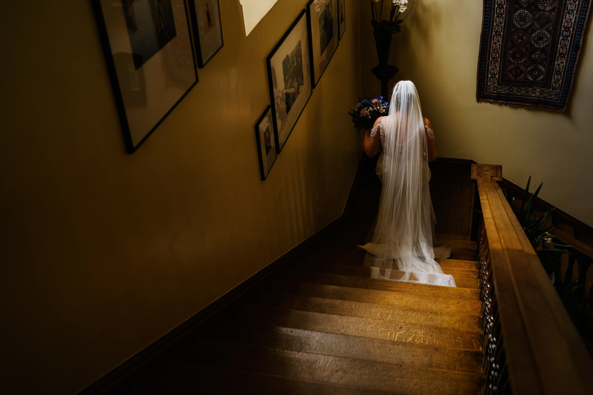 Norfolk Wedding Venue Photography at Gunthorpe Hall | The light from the window catches the bride as she walks down the stairs