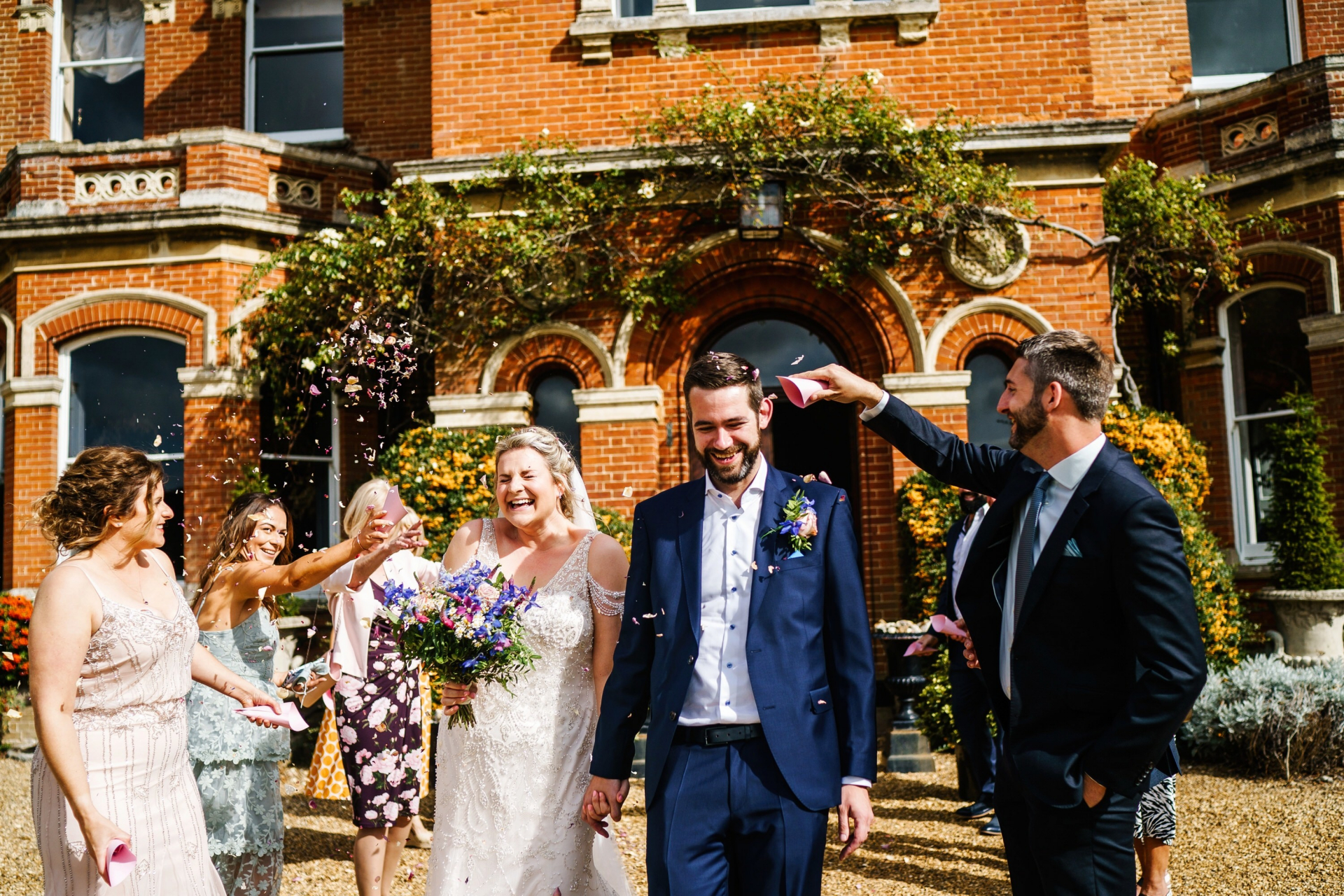 Gunthorpe Hall Wedding Venue - Norfolk Photos |  the bride and groom exit the hall into the bright outdoors