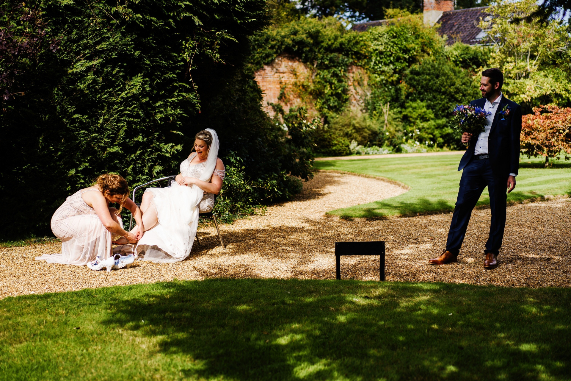 Wedding Photos Gunthorpe Hall | The bridesmaid helps the bride into her shoes outside