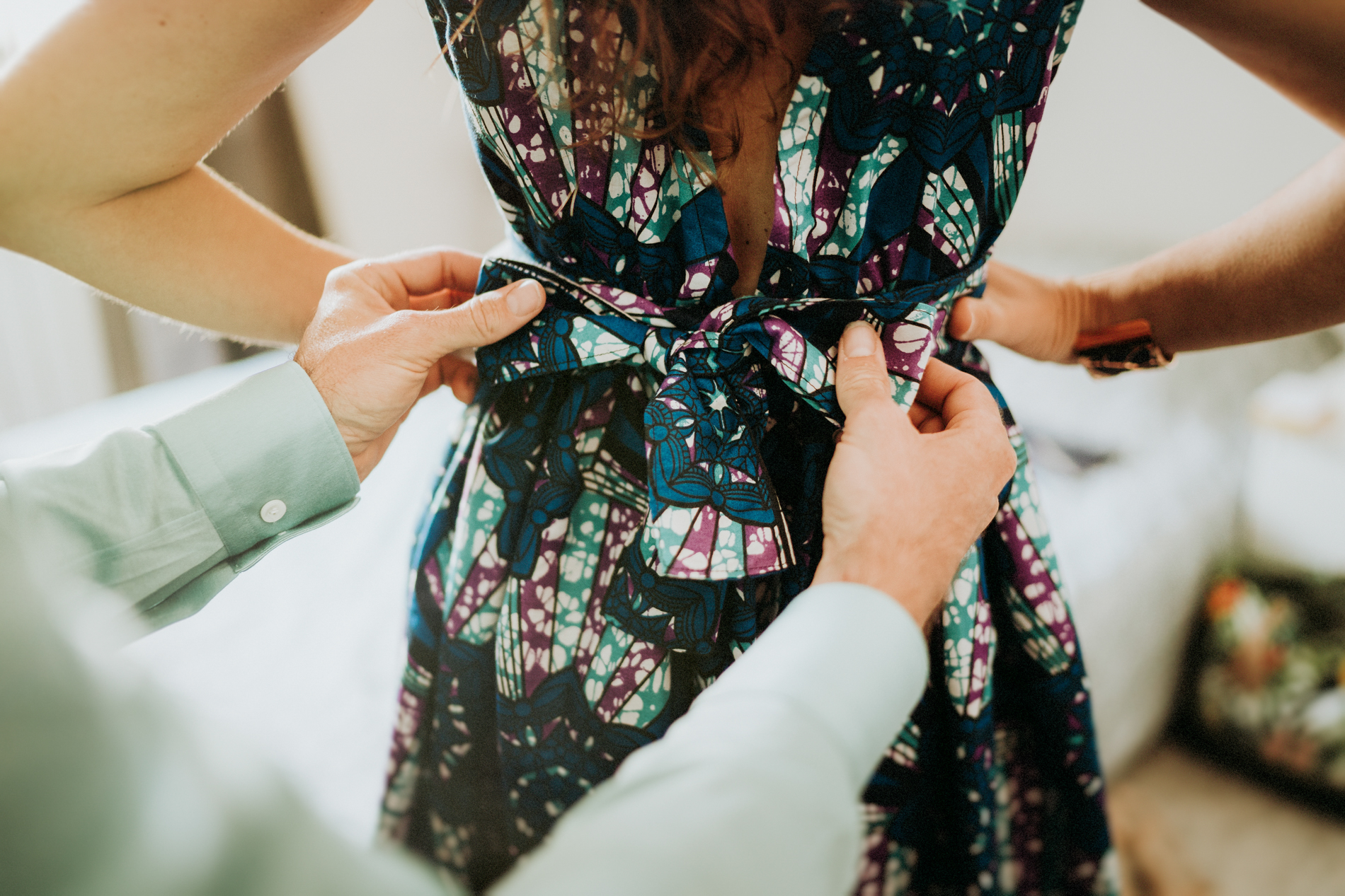 Wedding Photography for Lyon, FR | The groom helps his future wife tie a bow at the back of her dress