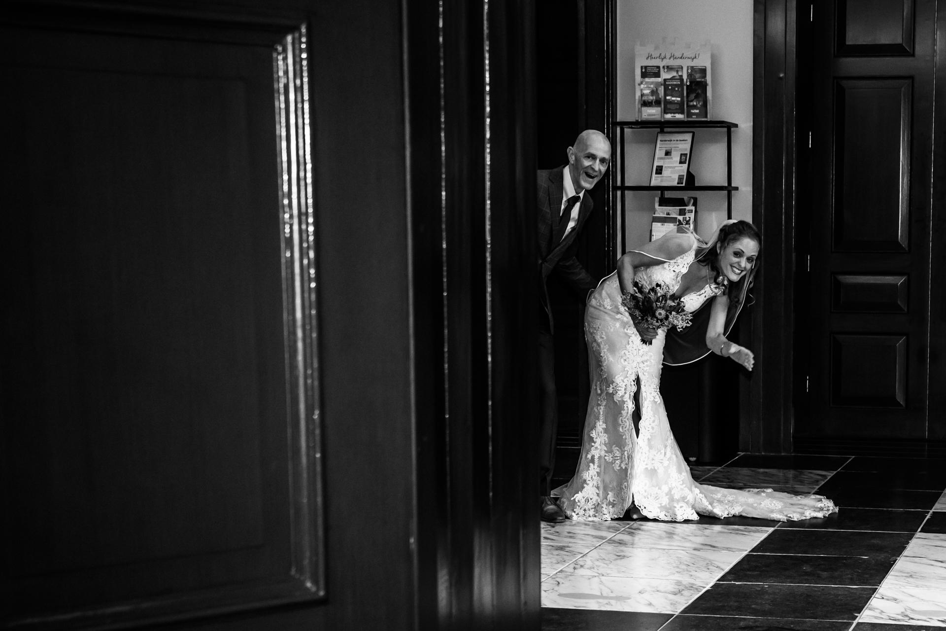 Oude Stadhuis à Harderwijk Town Hall Image de mariage | la mariée curieuse et son père, attendant dans le couloir avant la cérémonie