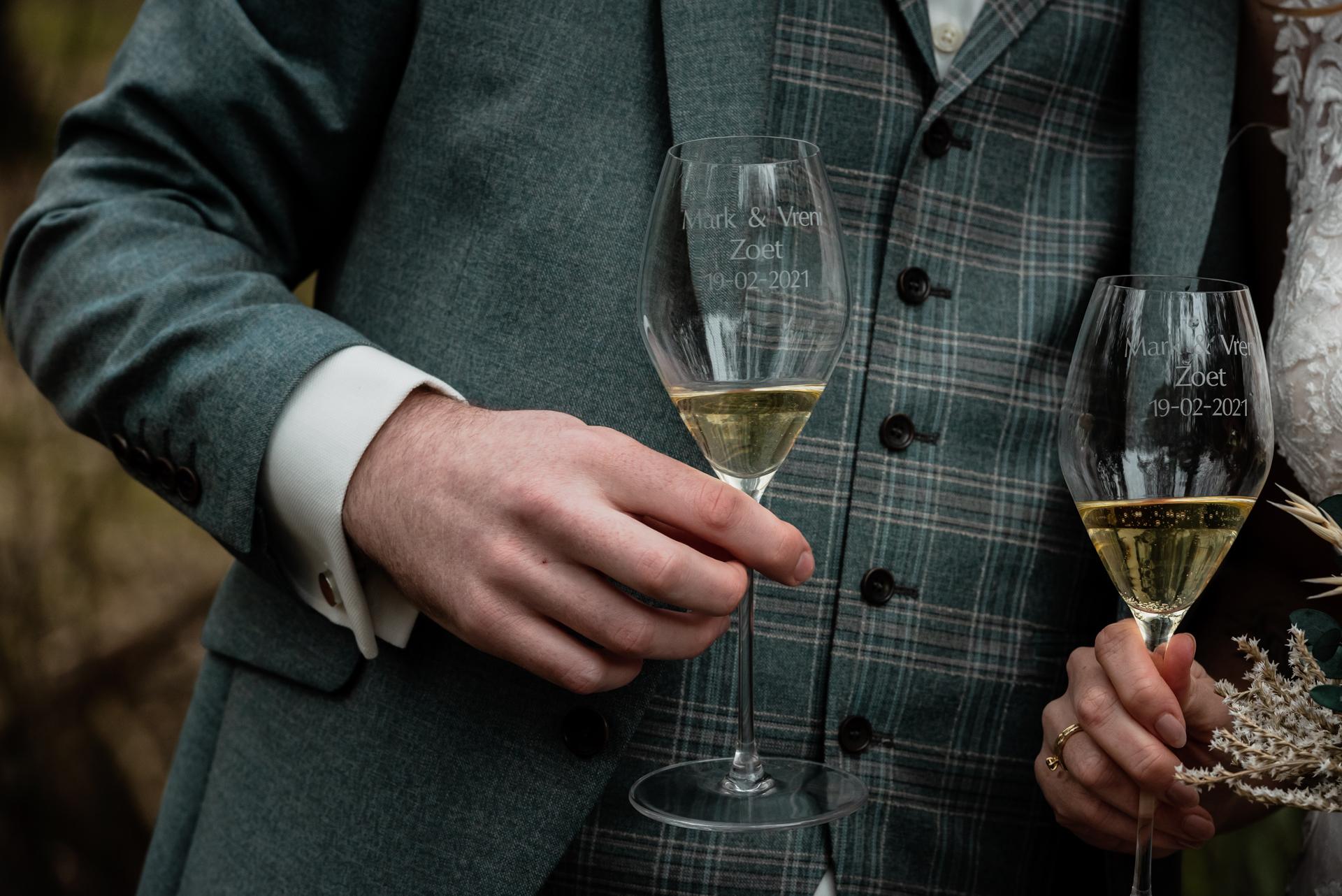 NL de détail de mariage Photo de Strokerbos, Harderwijk | Les mariés montrent la paire de lunettes magnifiquement gravées