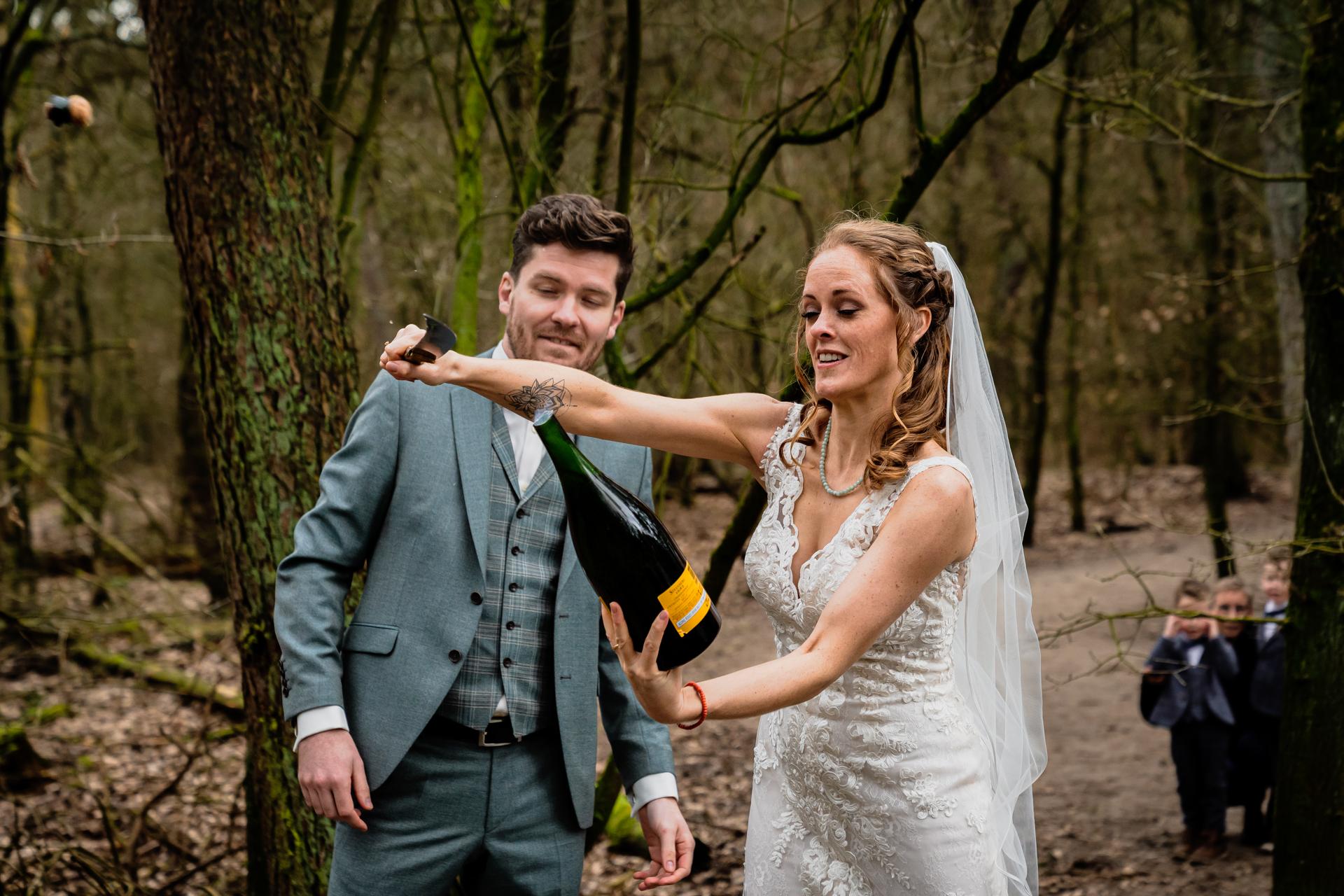 NL - Photographe de mariage à Strokerbos, Harderwijk | La mariée utilise habilement un couteau pour faire sauter le bouchon de la bouteille de champagne