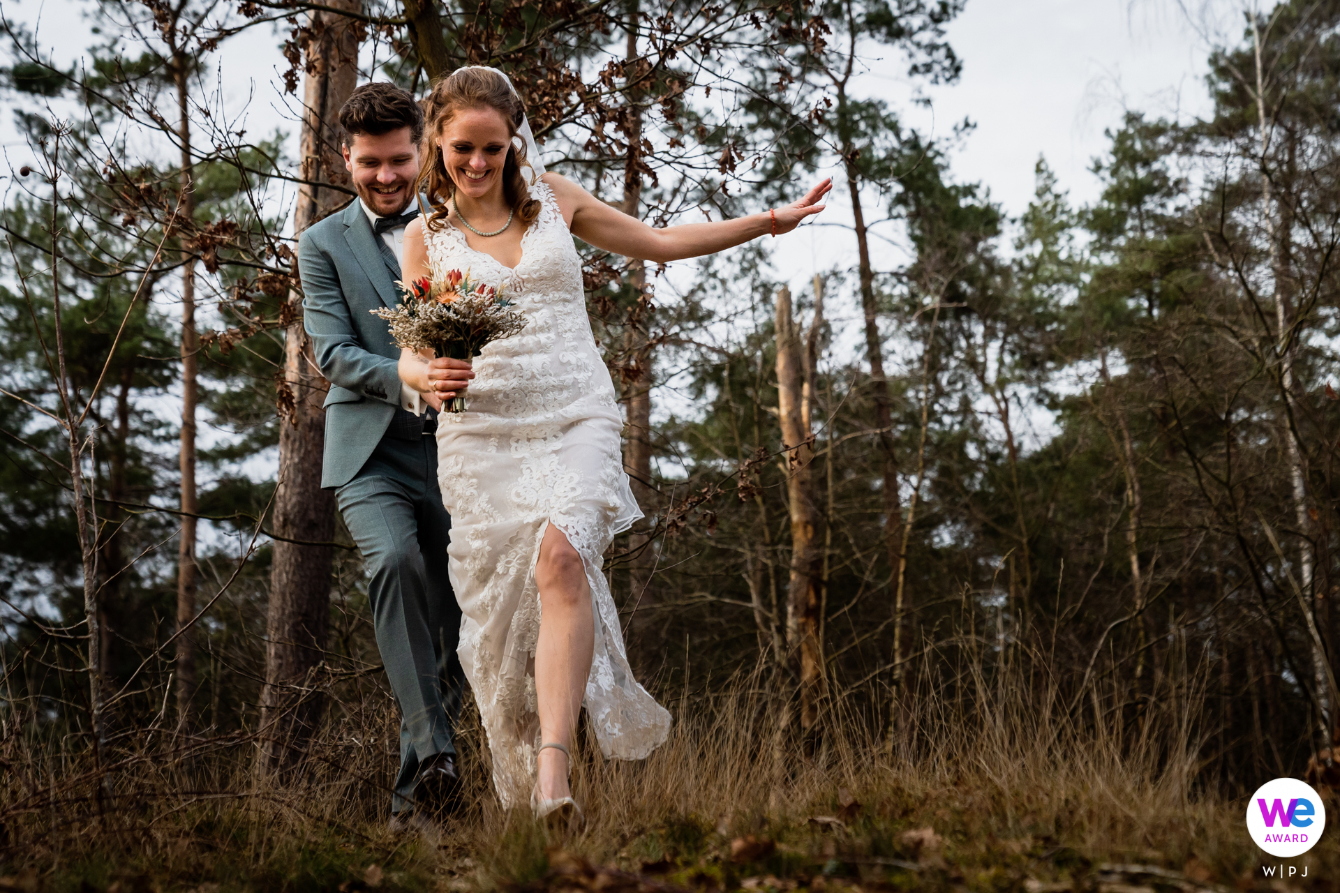 Photographes de mariage professionnels à Harderwijk | la mariée avait un peu de mal à traverser la forêt en talons hauts