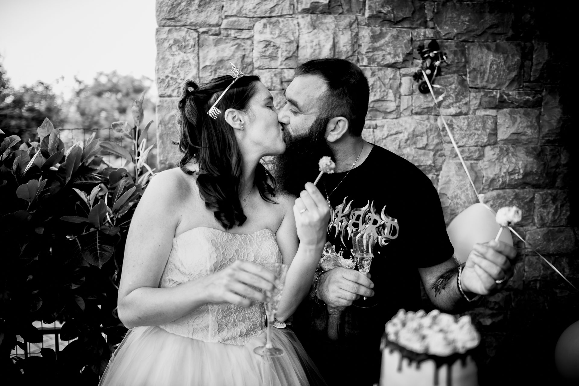 Brescia Backyard Wedding Reception Photography | champagne glasses in one hand and a piece of cake in the other