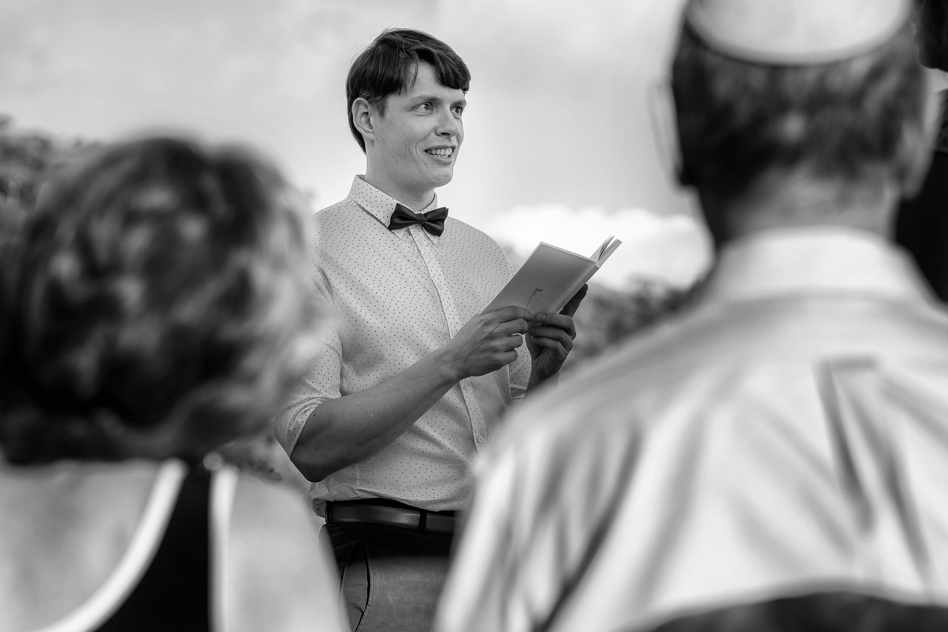 Costa Rica Outdoor Wedding Photography | The groom is using a small book as a reference
