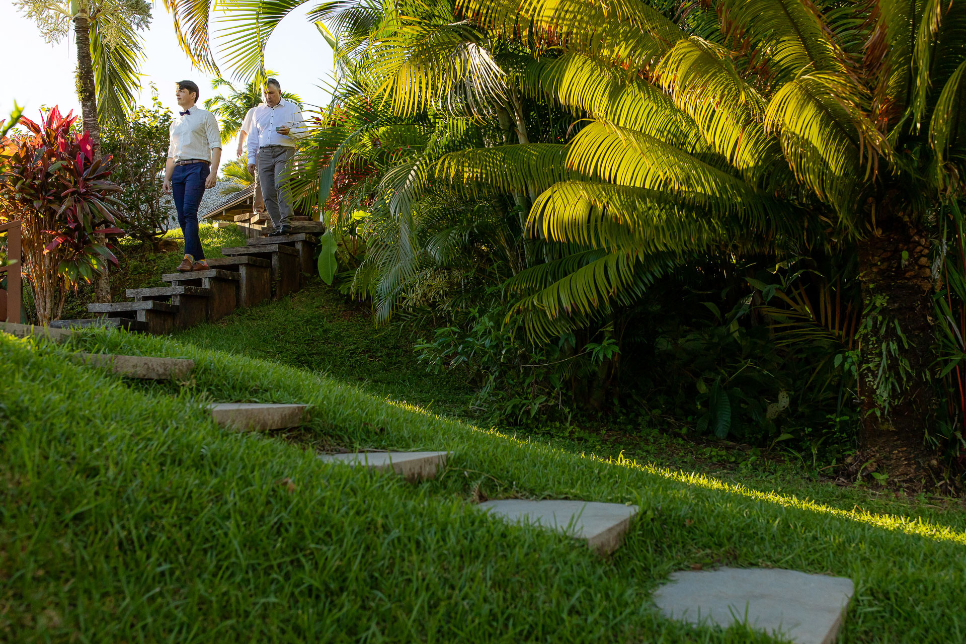 Costa Rica Wedding Photographer | The groom walks down the steps past the local flora and fauna at the outside ceremony