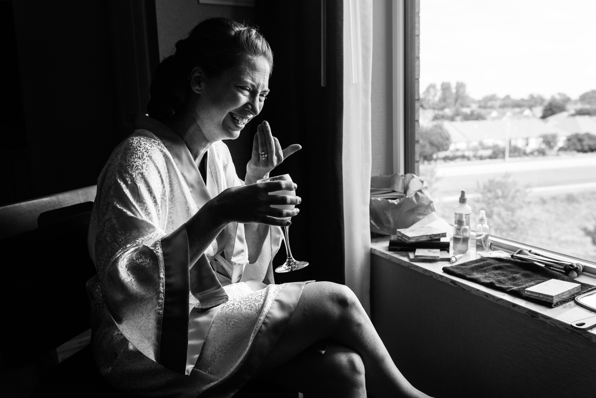 Pro Canadian Wedding Photographer of Ottawa | The bride laughs with a drink by the window