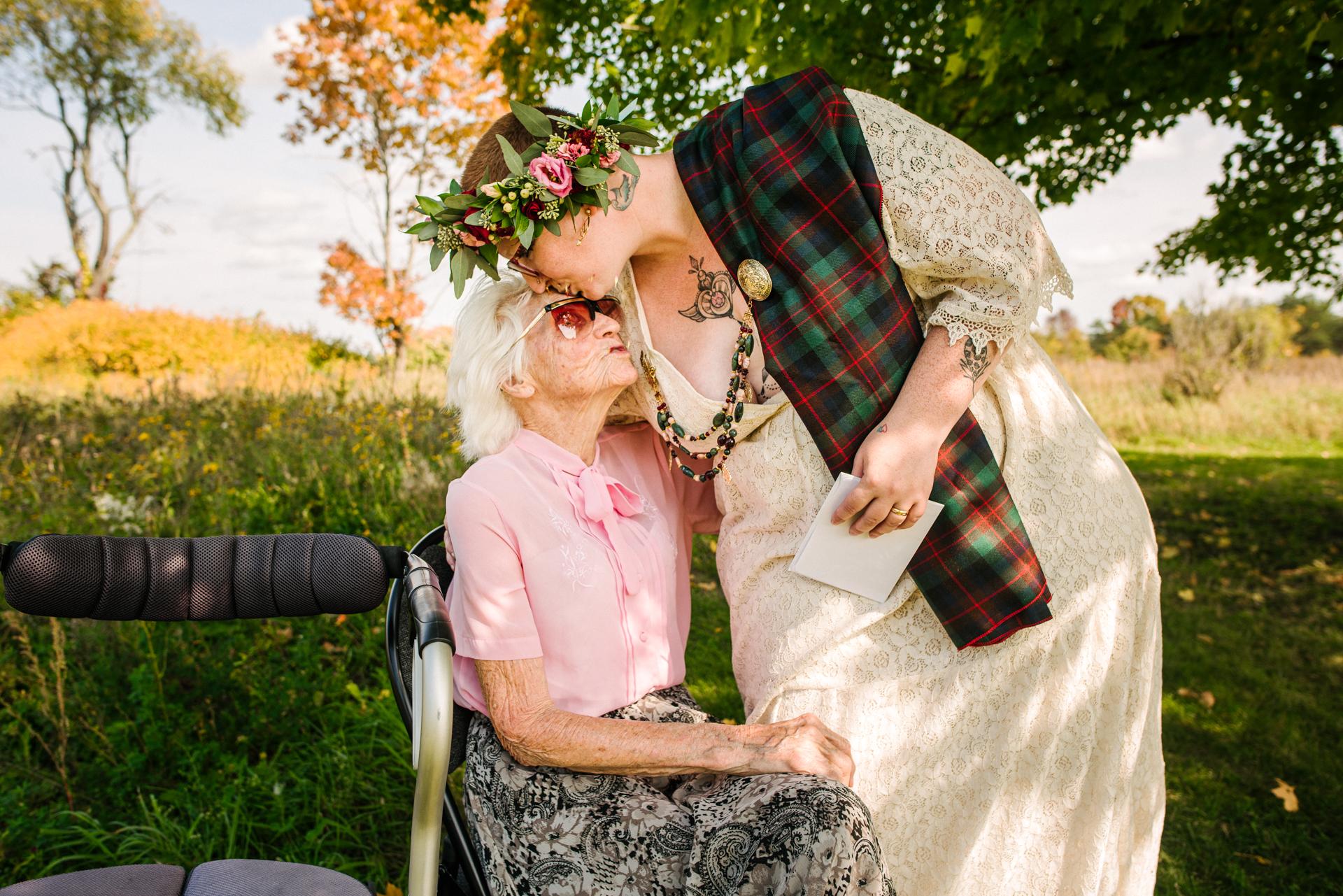 Fotografia de casamento ao ar livre em Ontário | A noiva se inclina para beijar a avó