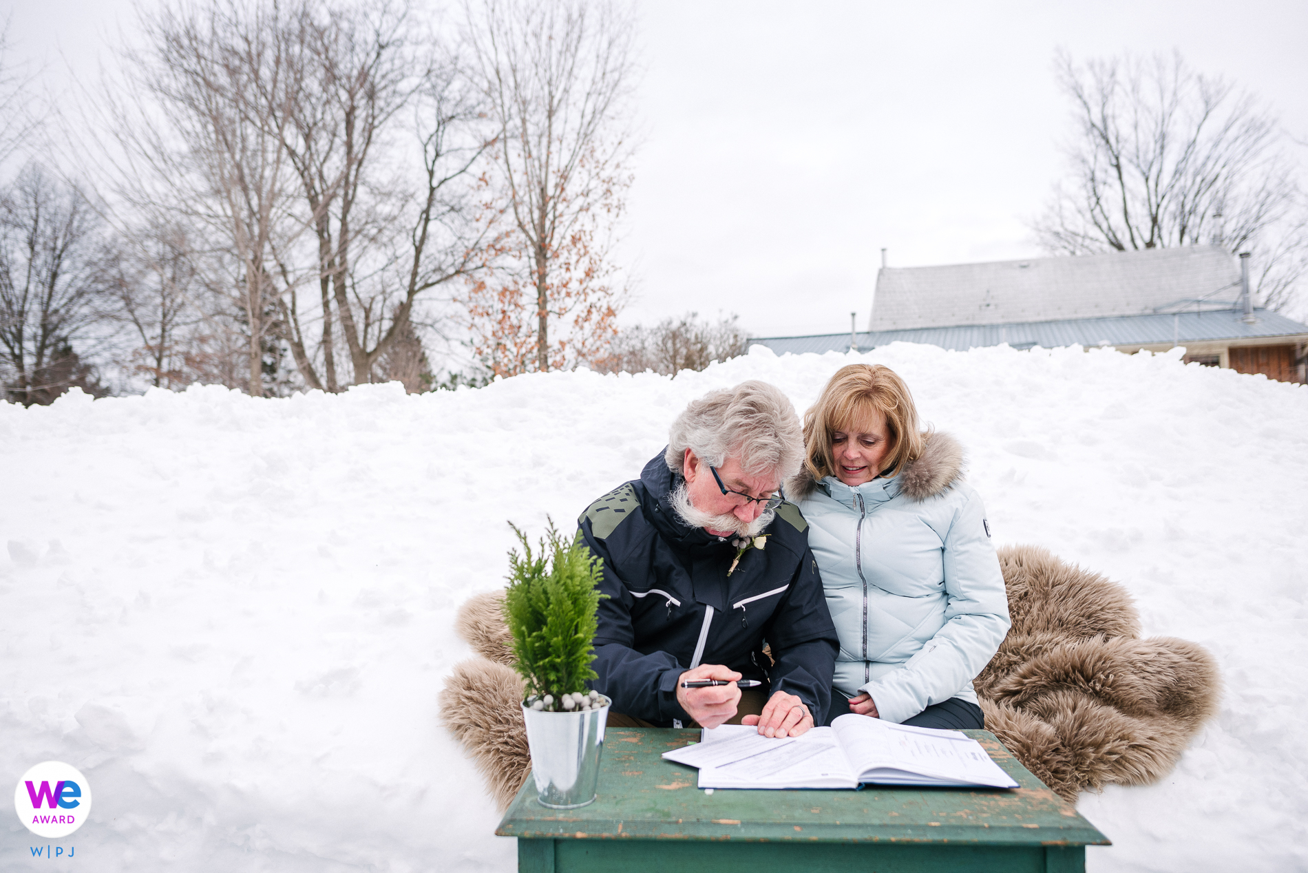 Rockport, Ontario, Thousand Islands Winter Wedding Image | The couple signs their papers, sitting on a blanket in the snow