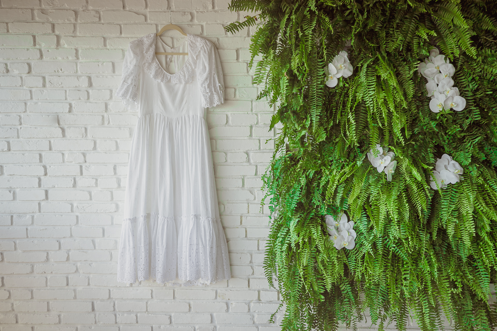 Maceio, Alagoas, Brazil Wedding Gown Detail Image | The bride's dress hangs on a wall