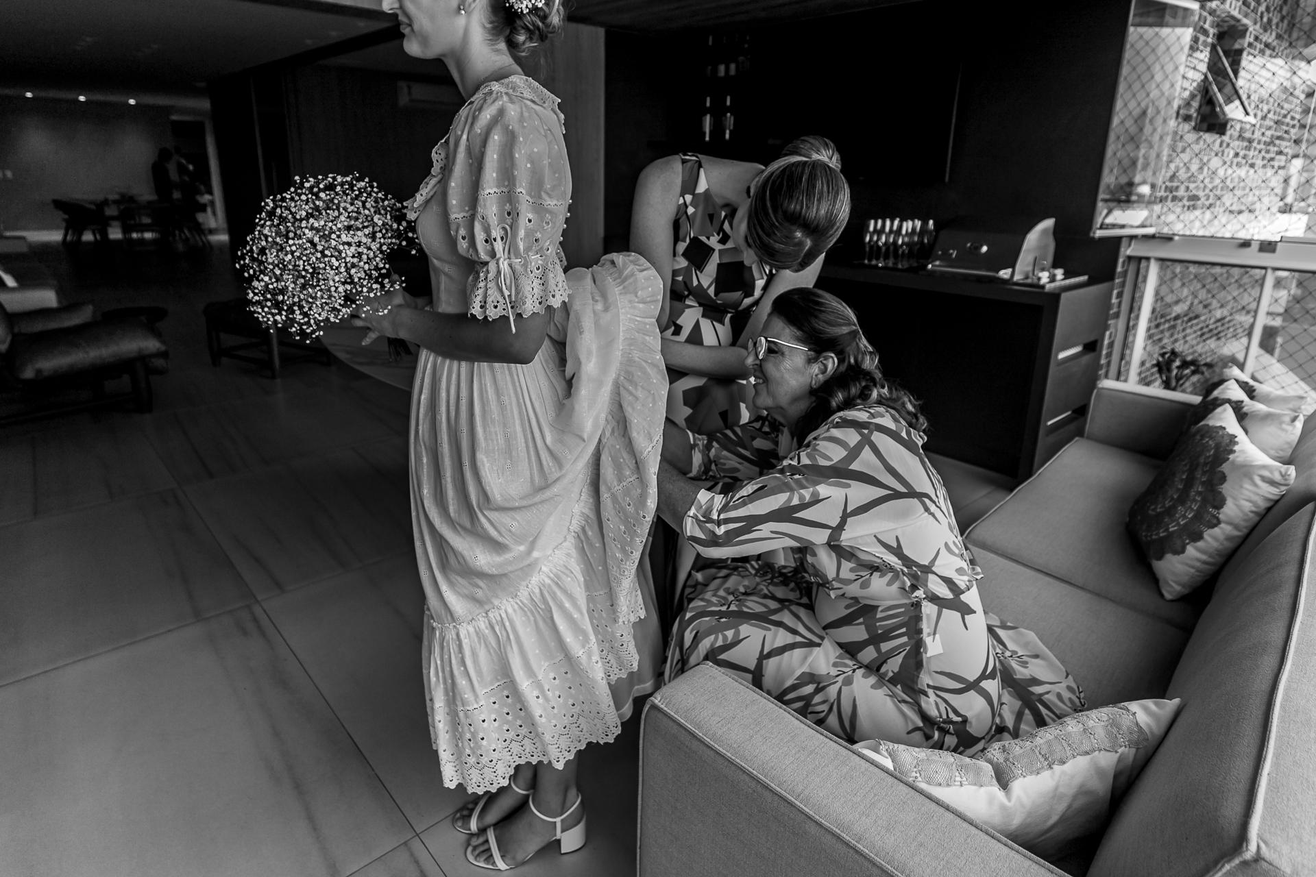 Maceio, AL, photo de fixation de robe de mariée du Brésil | La mère et la soeur de la mariée s'affairent avec sa robe et s'assurent qu'elle a l'air bien
