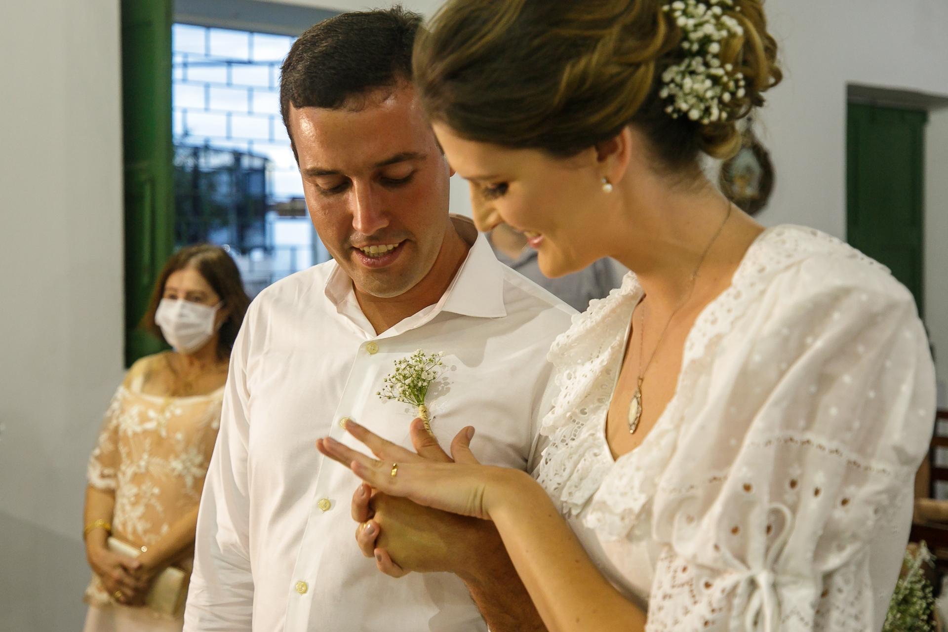 Cérémonie de mariage photo à AL, Brésil | La mariée sourit et admire sa nouvelle alliance