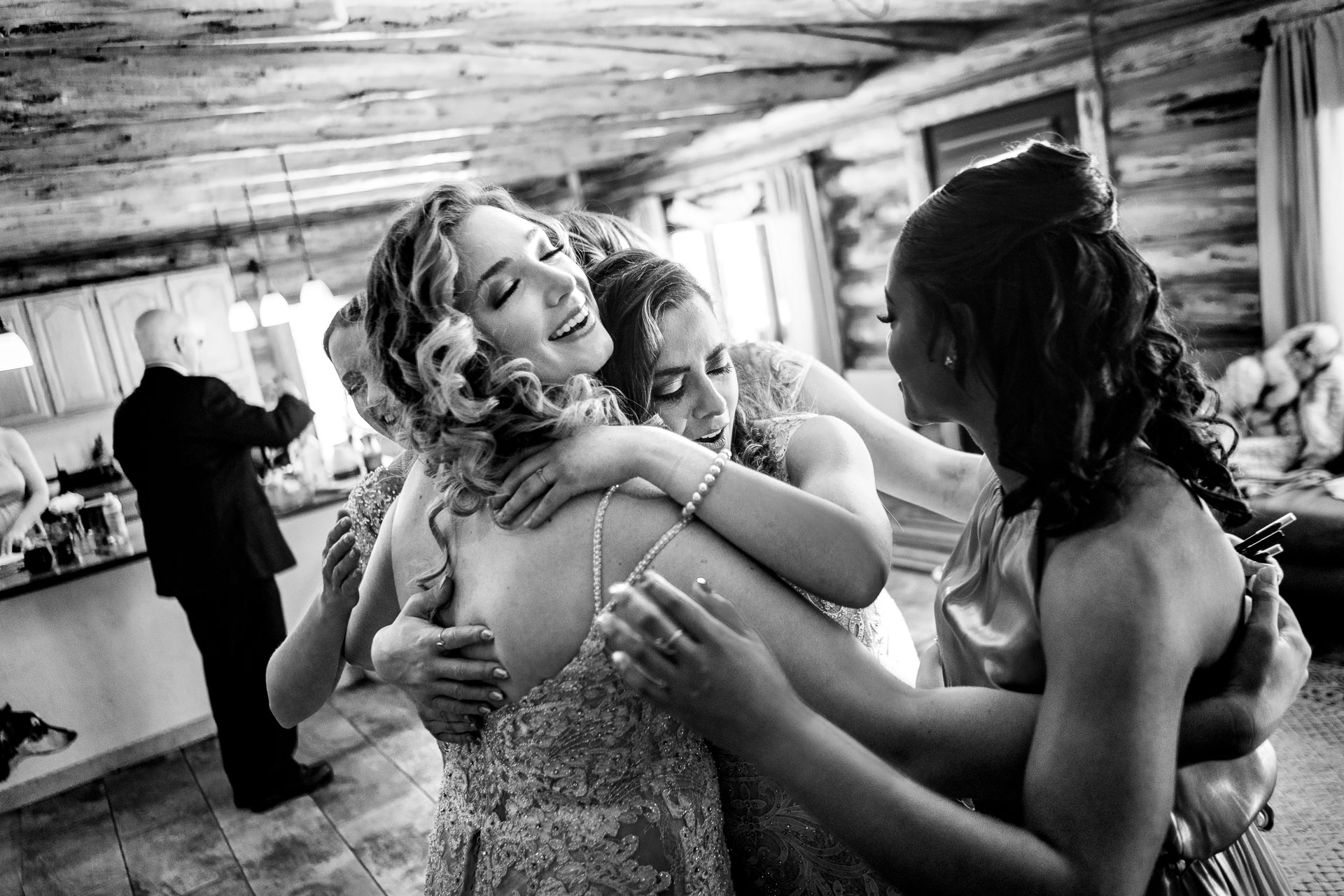 Pagosa Springs Wedding Venue Photo - Snow Wolf Lodge | A bridesmaid embrace the bride with tears of joy