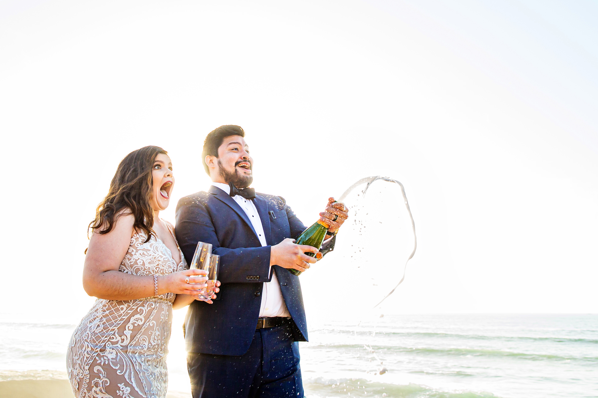 Sunset Cliffs Intimate Wedding Photographer of CA | The groom pops a bottle of champagne to toast his new bride