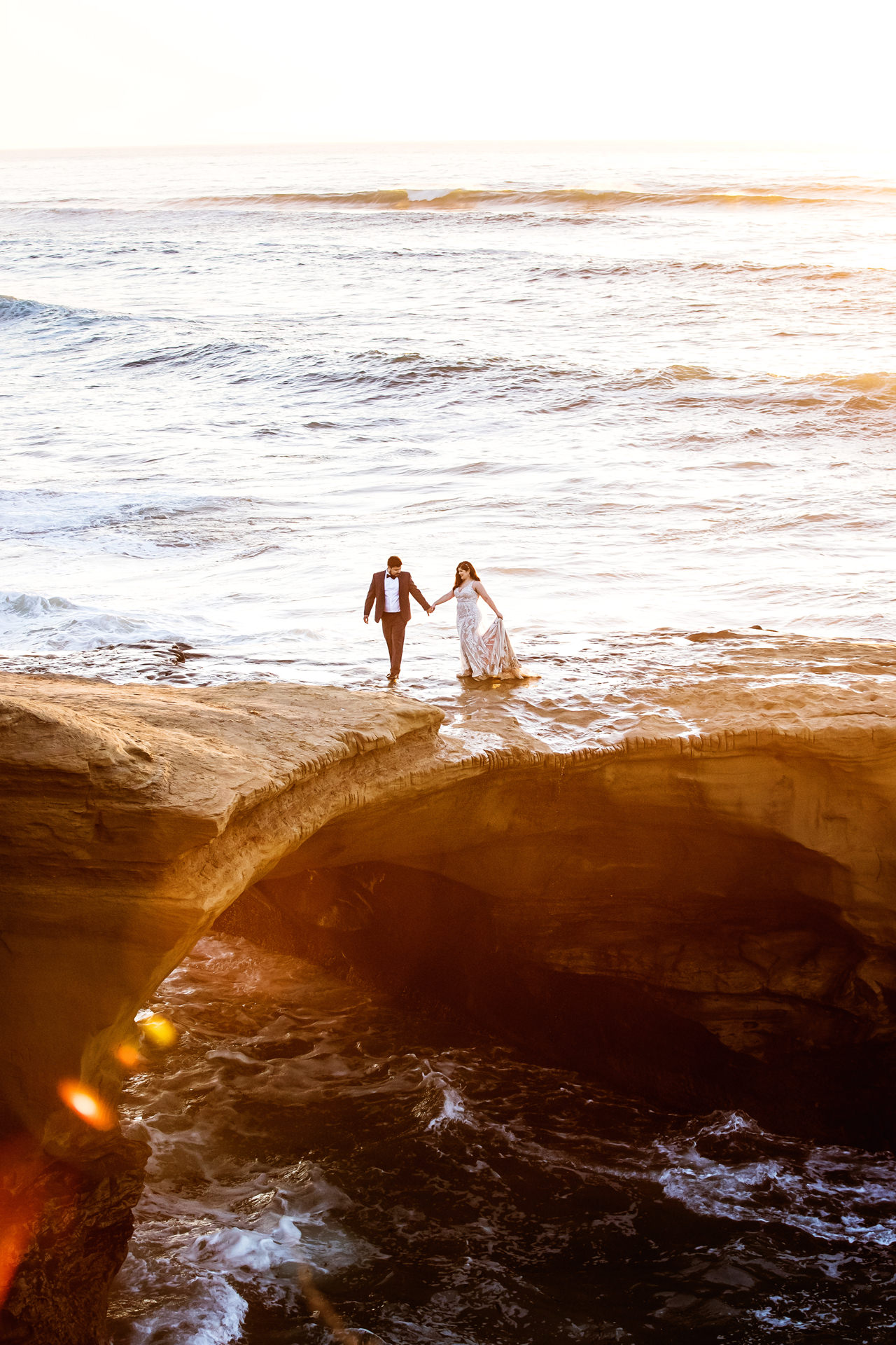 Sunset Cliffs Couple Portrait Session | Hand in hand as they cross the beach cliffs together
