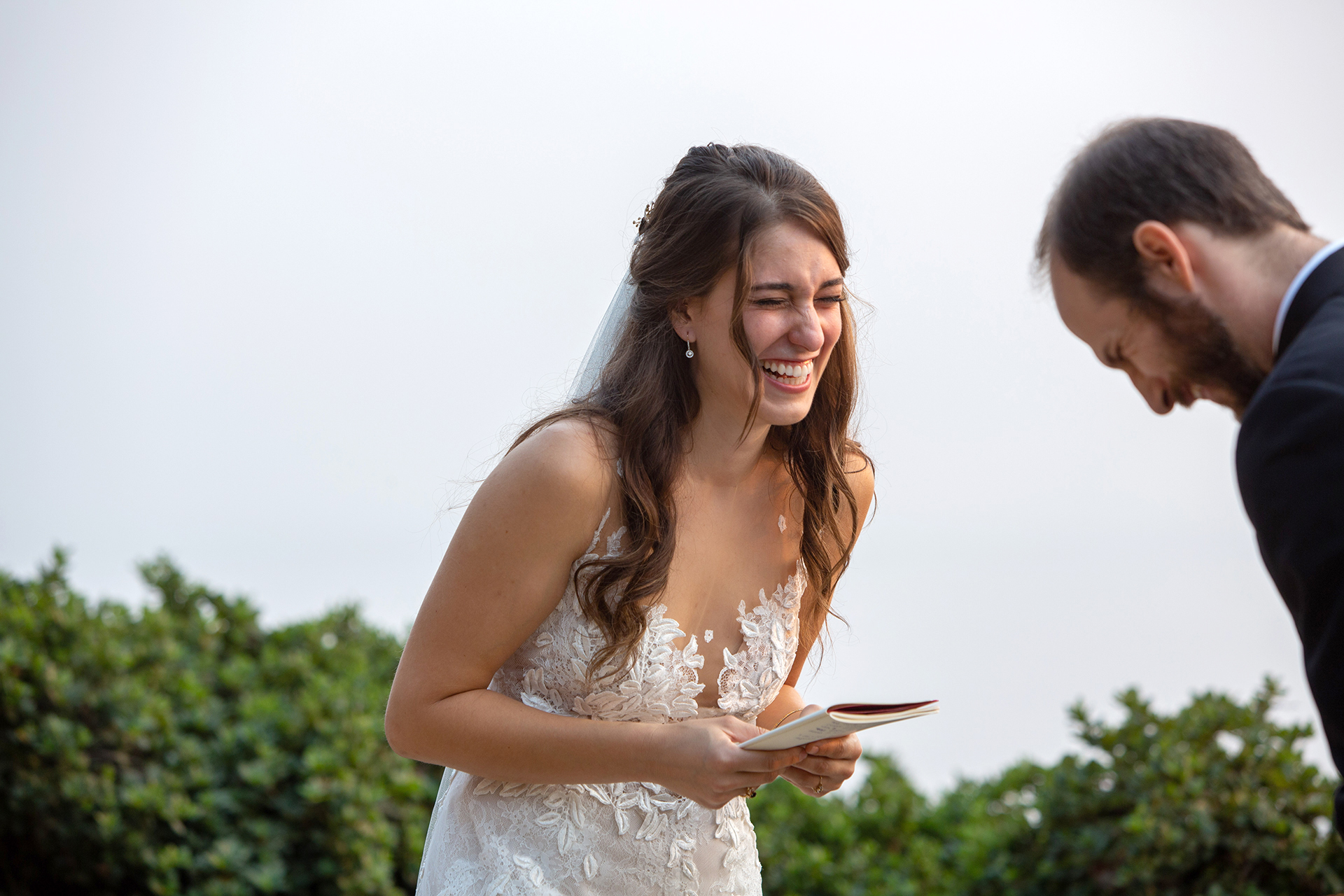Coastal Big Sur Wedding Ceremony - Wind and Sea Photos | The couple bursts into laughter during the vow exchange