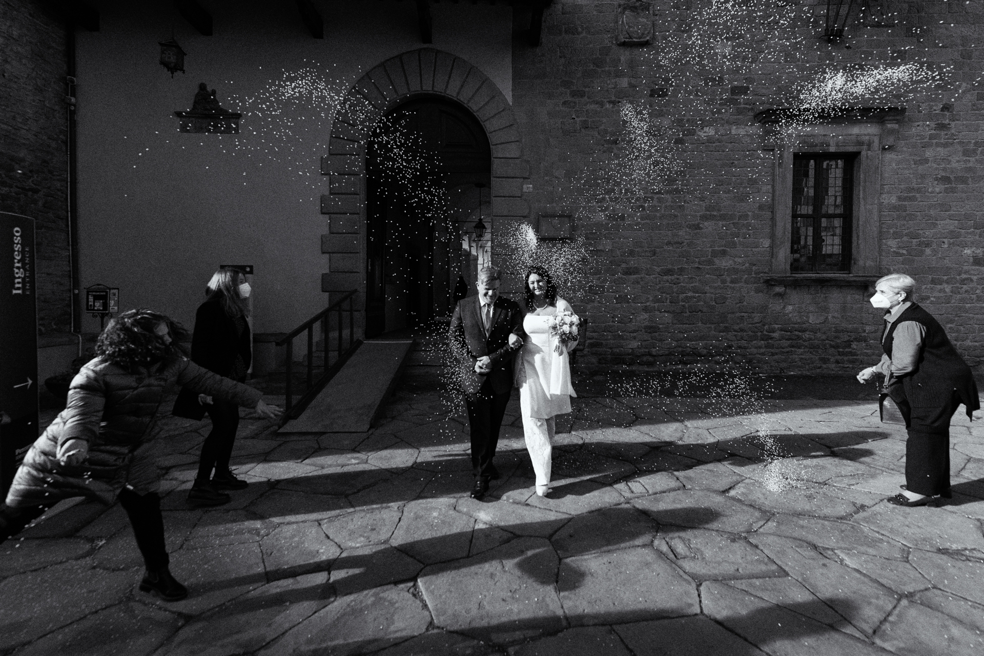 Foto de celebración de boda en el ayuntamiento de Arezzo | varios invitados a la boda arrojan arroz a la pareja después de la ceremonia