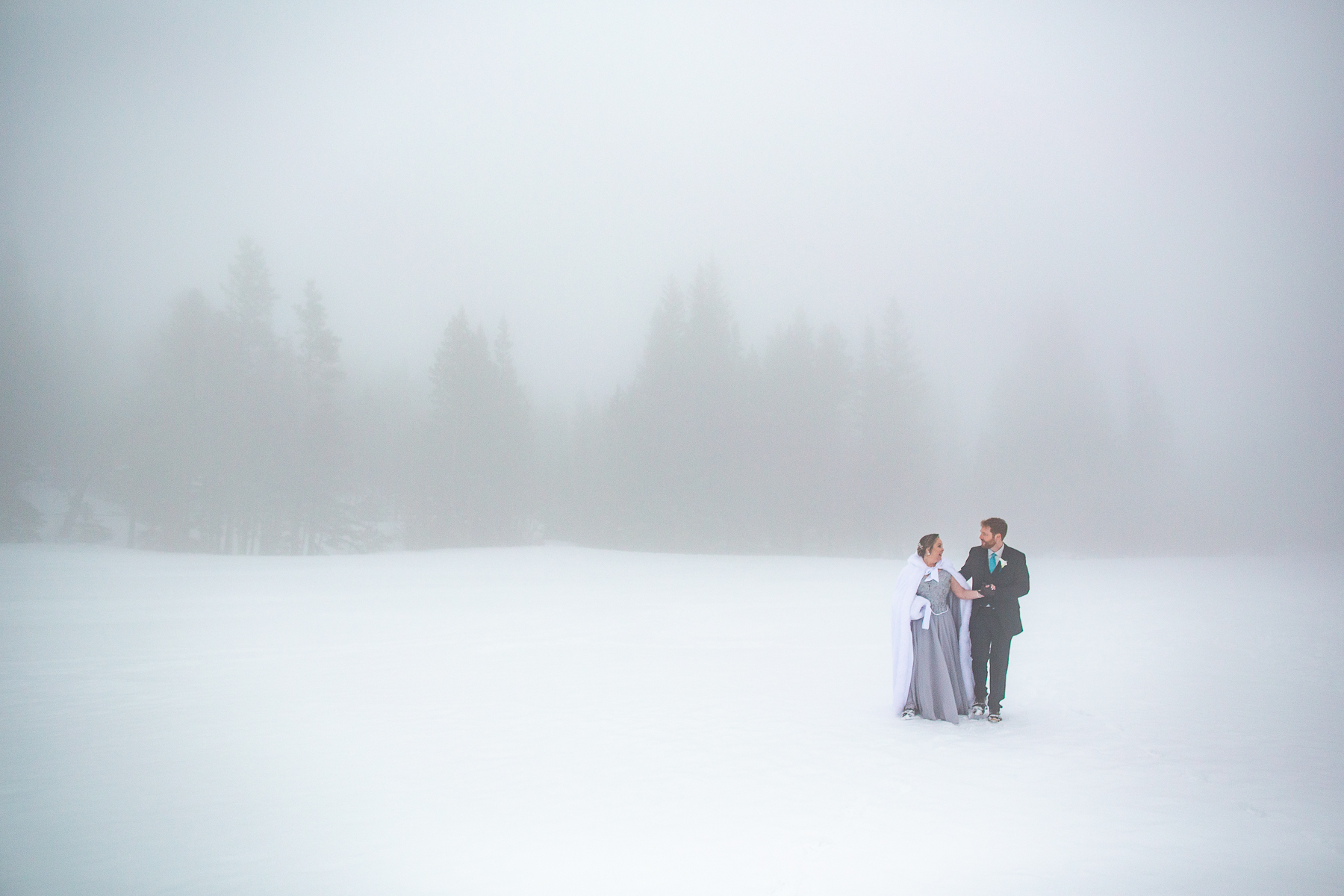 Bear Lake Wedding Shoot at Rocky Mountain National   The bride and groom walk across the fogged-in snowy lake