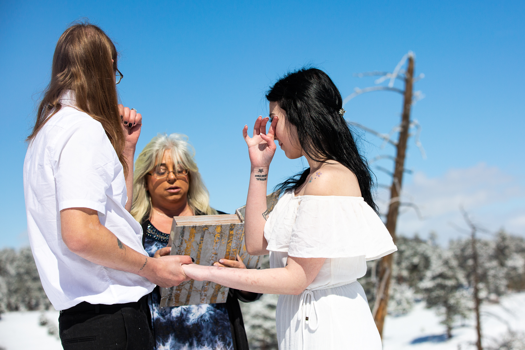Wedding and Elopement Photographers in Morrison, CO | The bride wipes away a tear in the crisp morning air