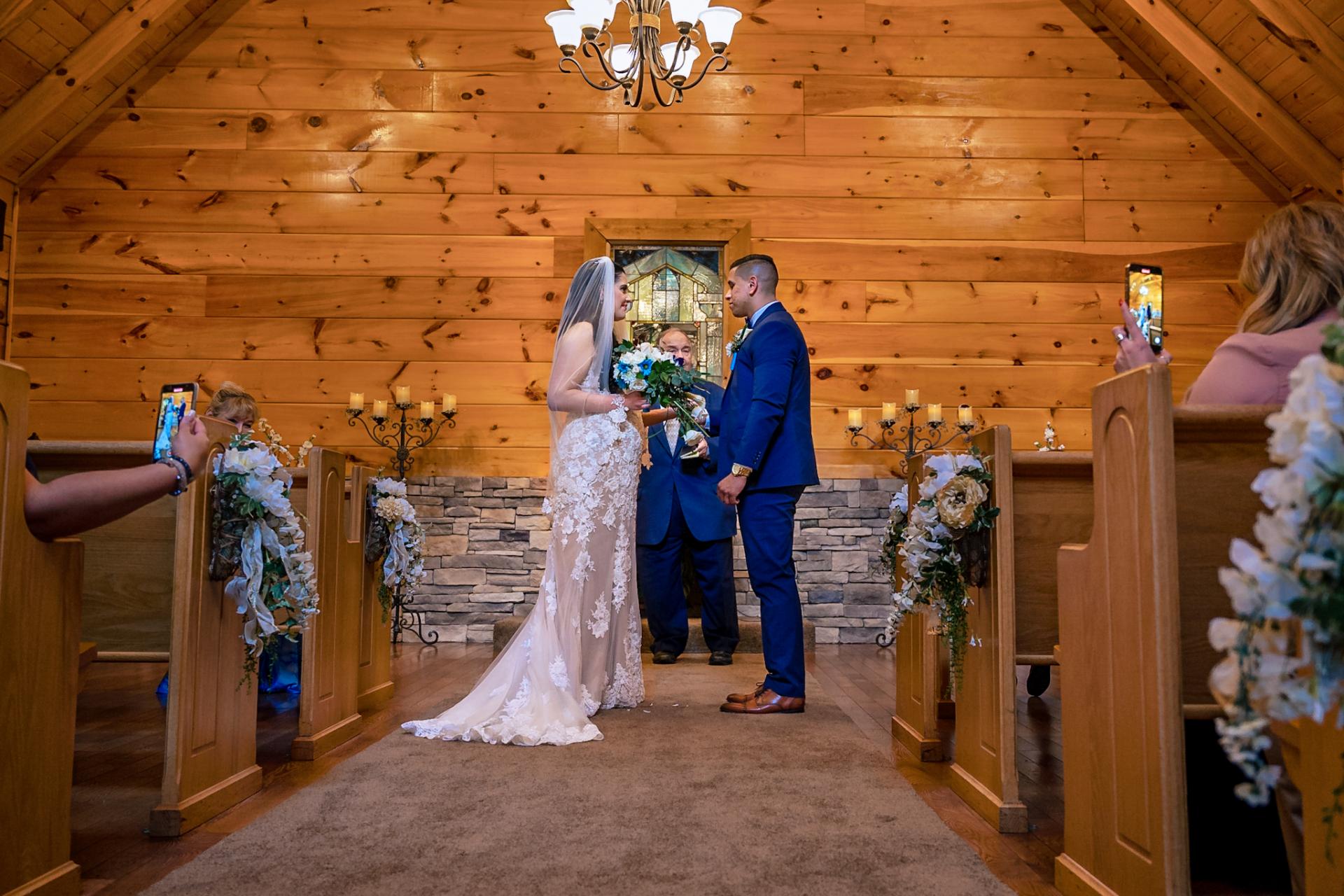 Pequeña capilla de troncos para bodas de Gatlinburg | Imagen de la novia y el novio uno frente al otro durante la ceremonia