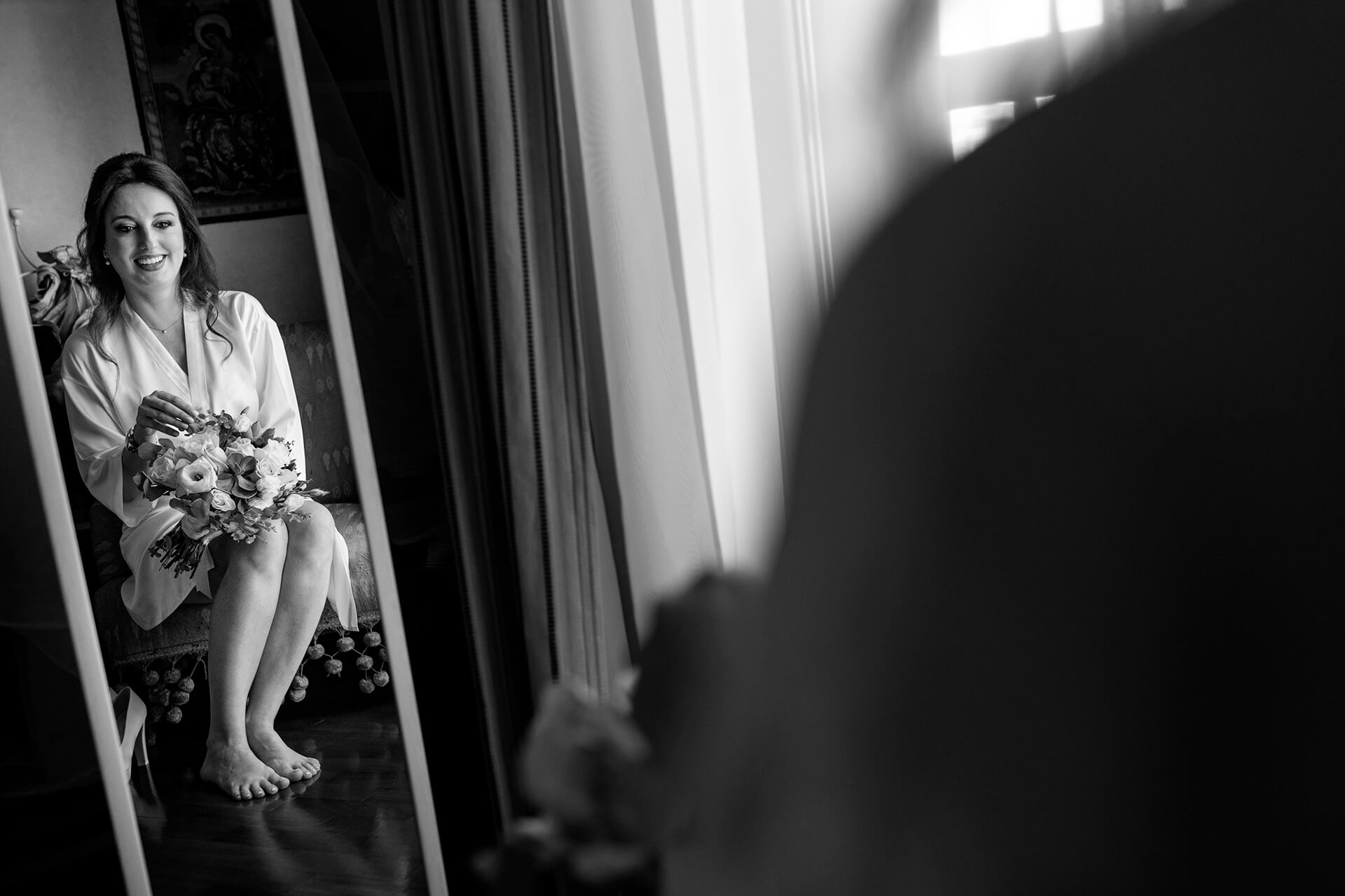 Italian Wedding Photography - Bride Getting Ready | with her bouquet in hand while she appreciates the work of the hairdresser