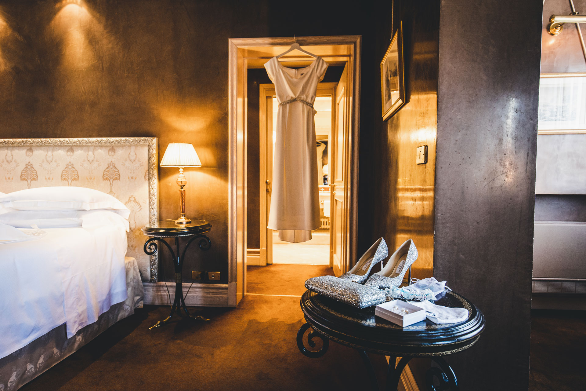 Elegant Wedding Photography from Hotel Bauer | the timeless and elegant wedding gown hanging in the doorway