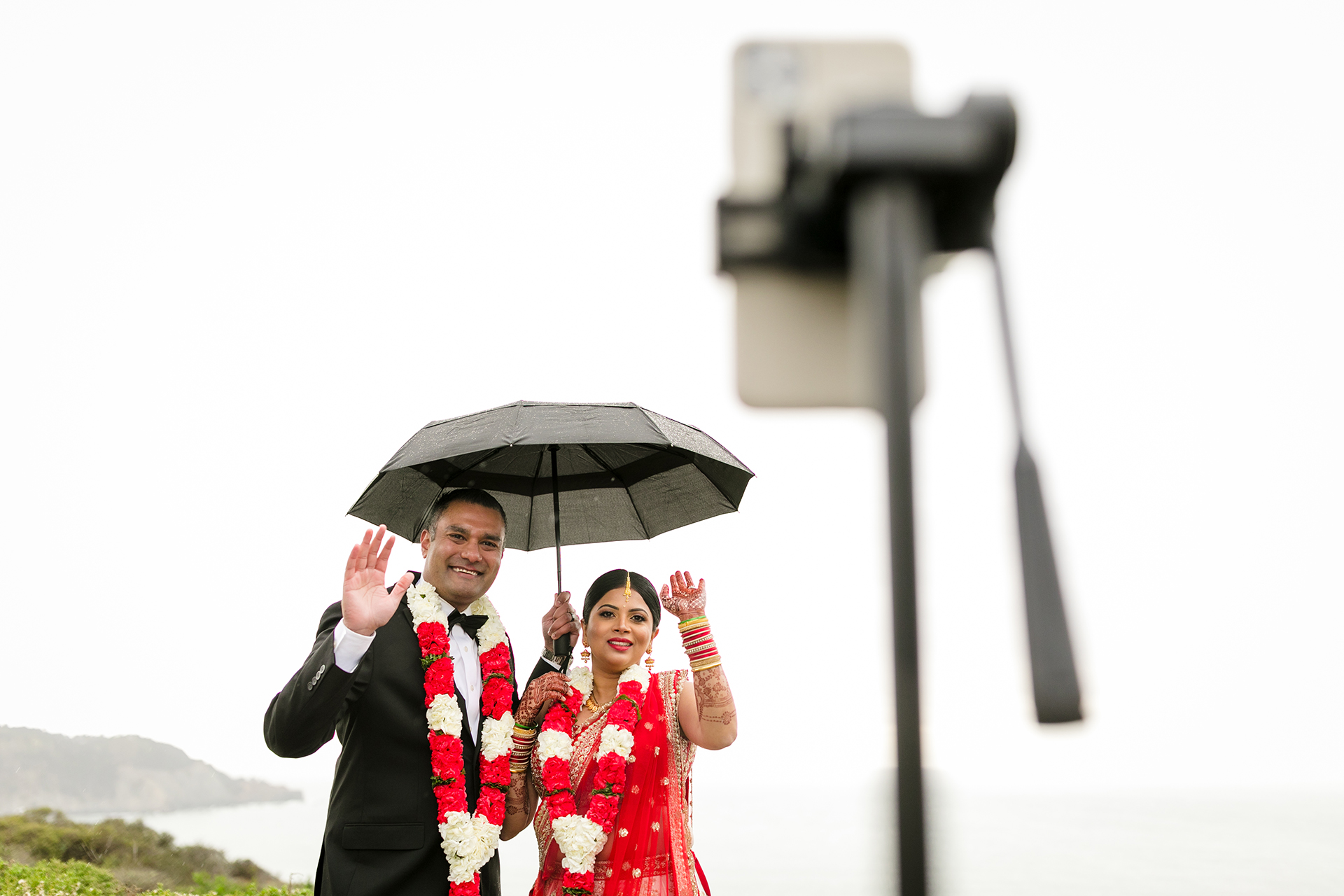Golden Gate Bridge and Marin Headlands Wedding Image | Holding an umbrella to shelter themselves from the rain