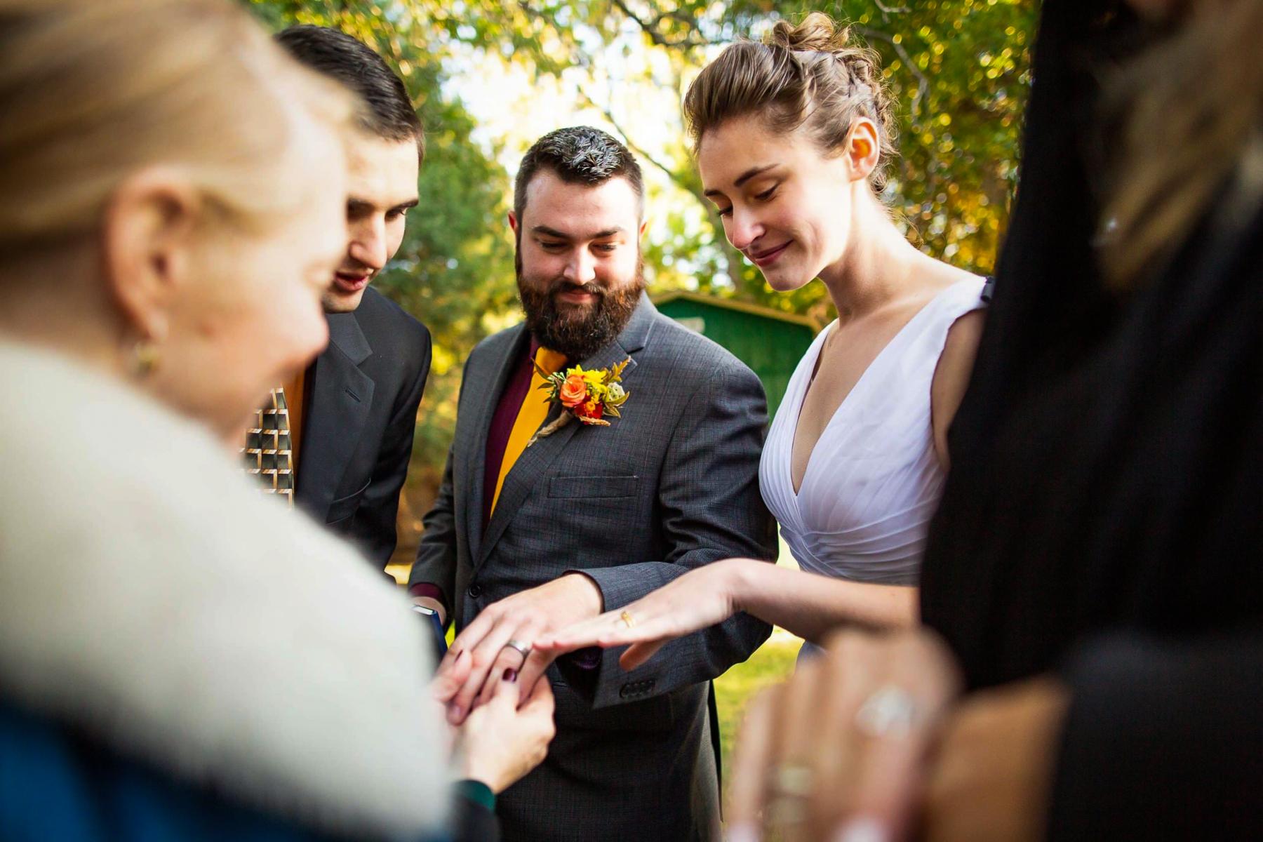 Kreative Hochzeitsfotografie in Colorado | Die wenigen Gäste bewundern die Pärchenringe