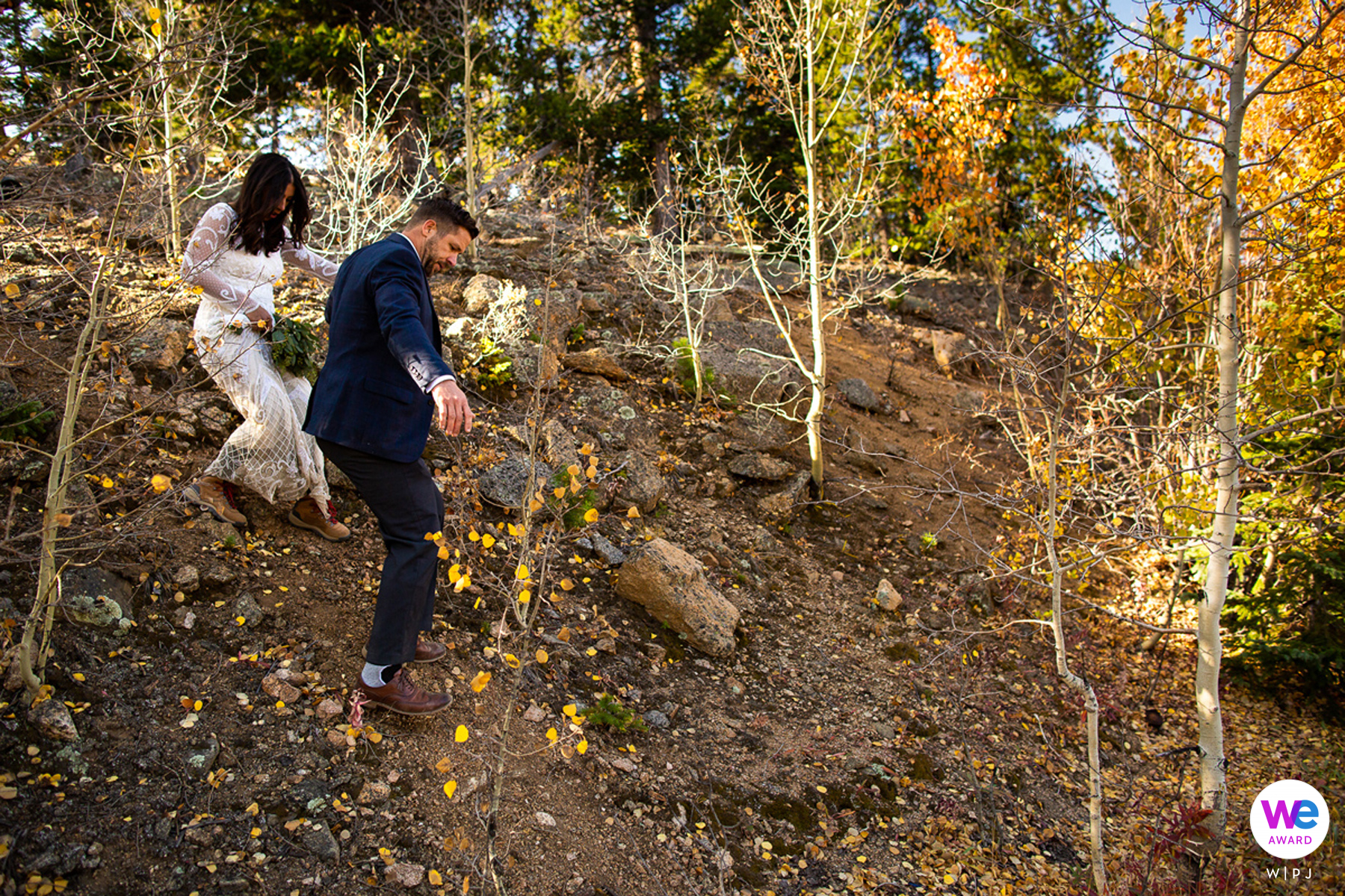 Mount Evans - Outdoor Ceremony Photography   The groom leads his new wife down the steep mountainside